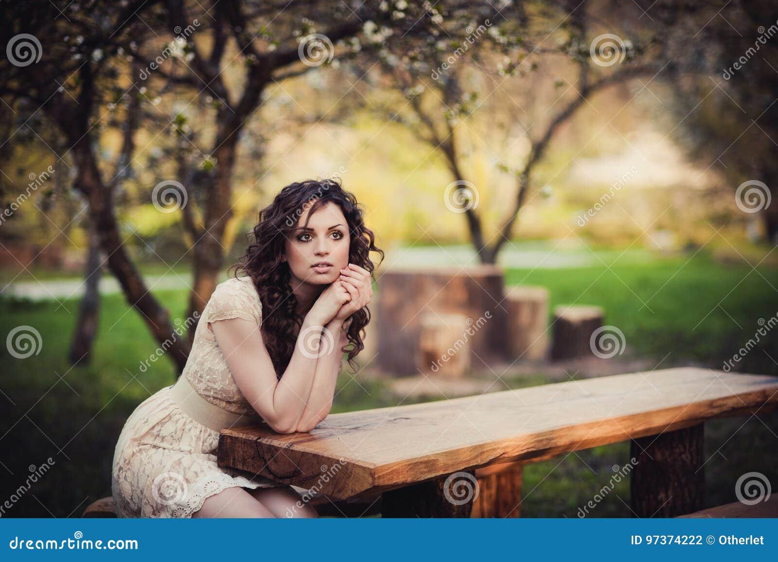 Ragazza castana dagli occhi castani che si siede su un banco