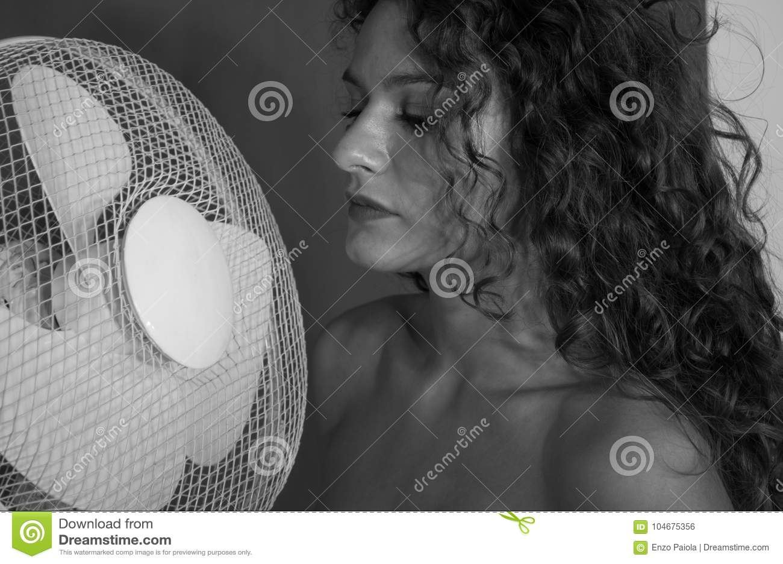 Ragazza castana sexy con capelli ricci con la ventola di raffreddamento