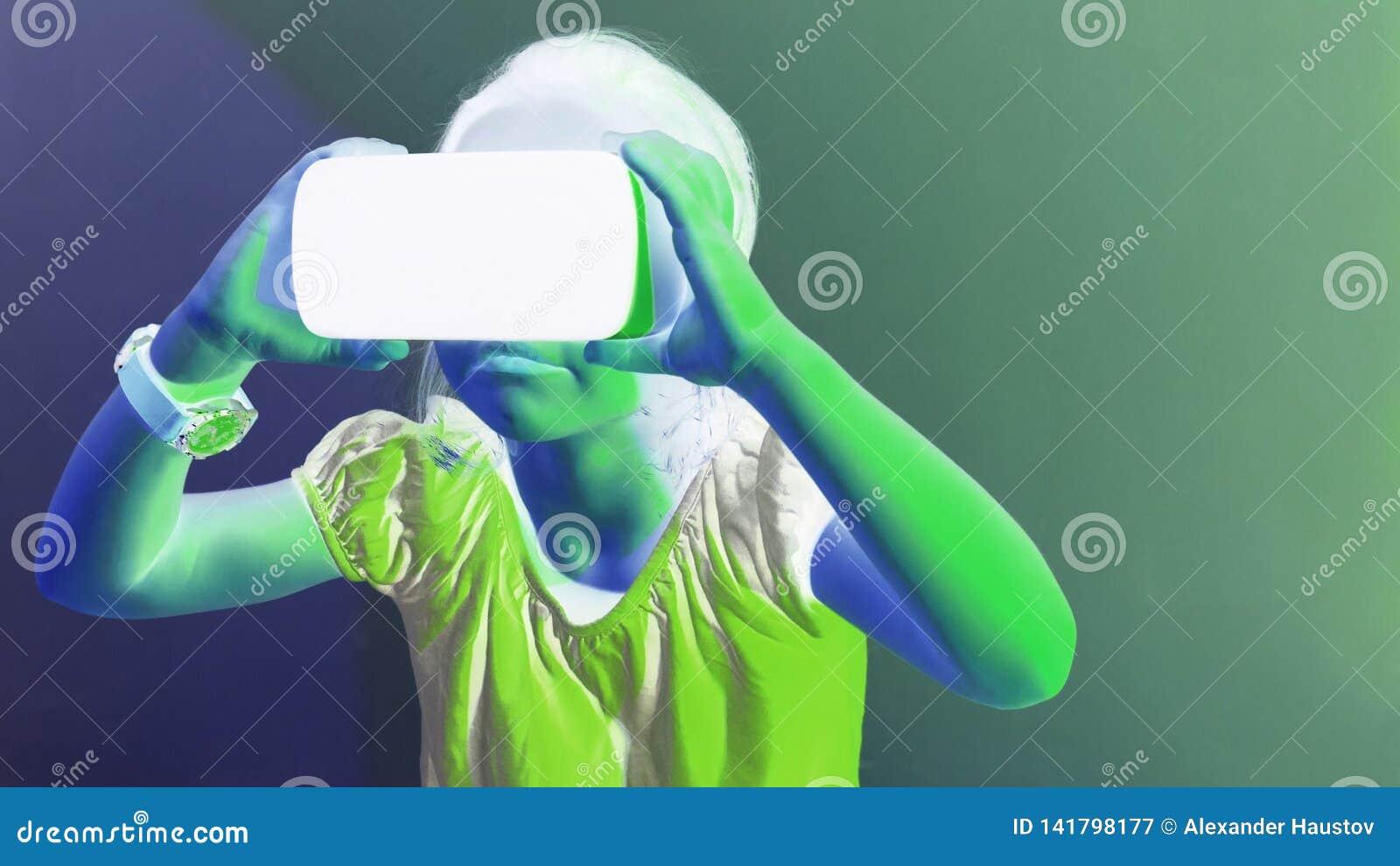 Ragazza che avverte il gioco della cuffia avricolare di VR su fondo variopinto Tecnologia virtuale