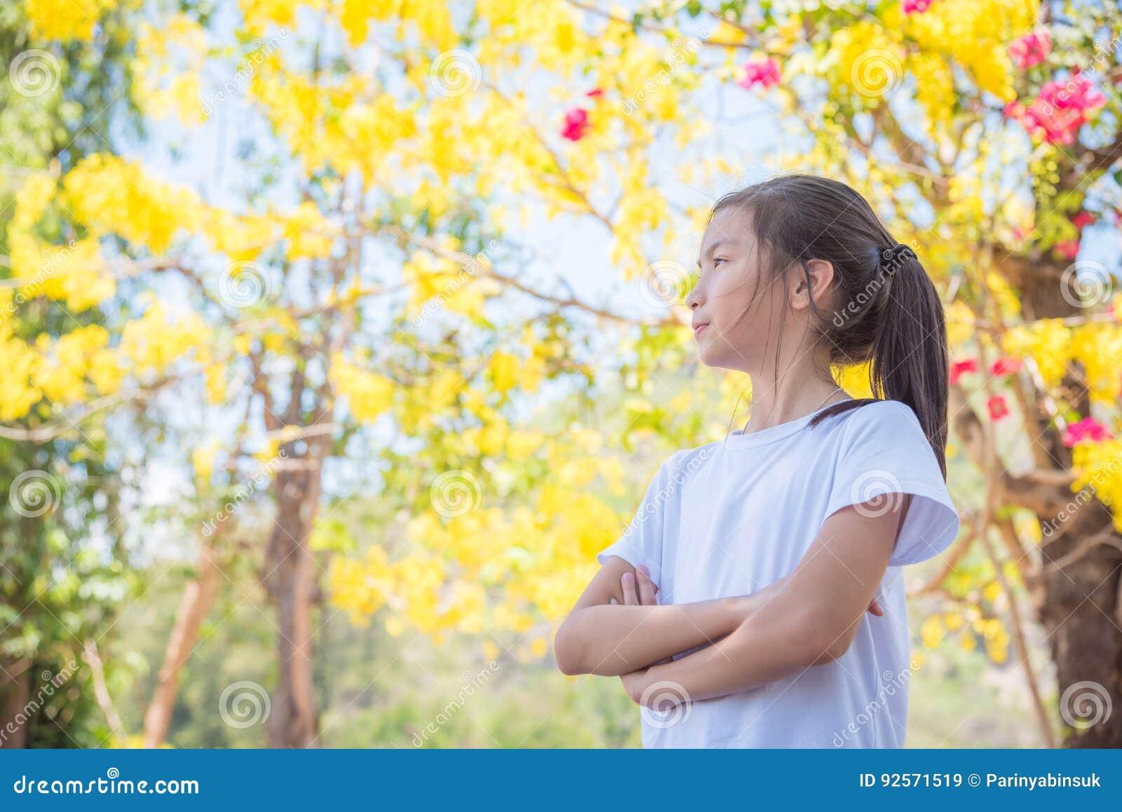Ragazza che esamina fiore in parco