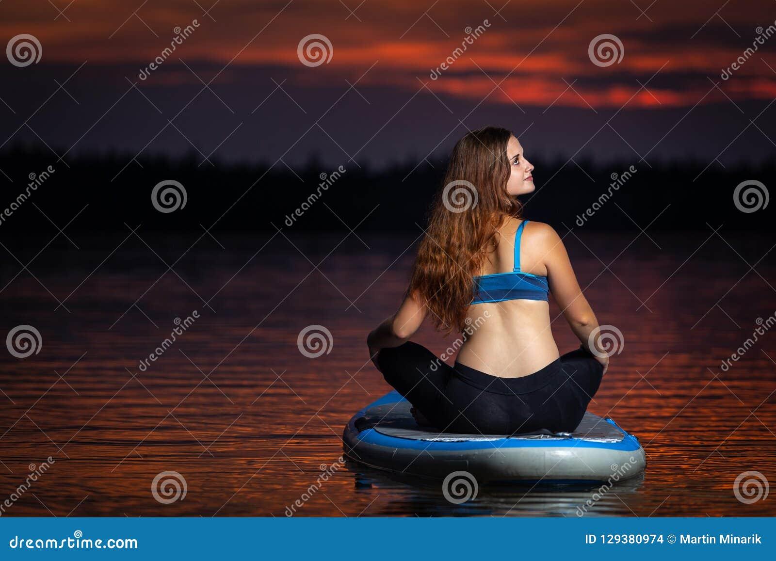 Ragazza che esercita yoga sul paddleboard nel tramonto sul lago scenico Velke Darko