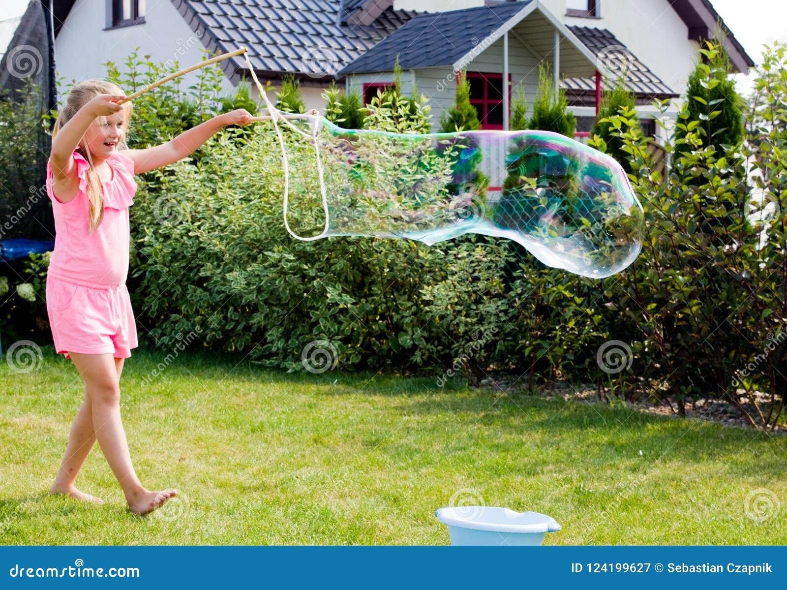 Ragazza che fa le bolle di sapone in giardino domestico