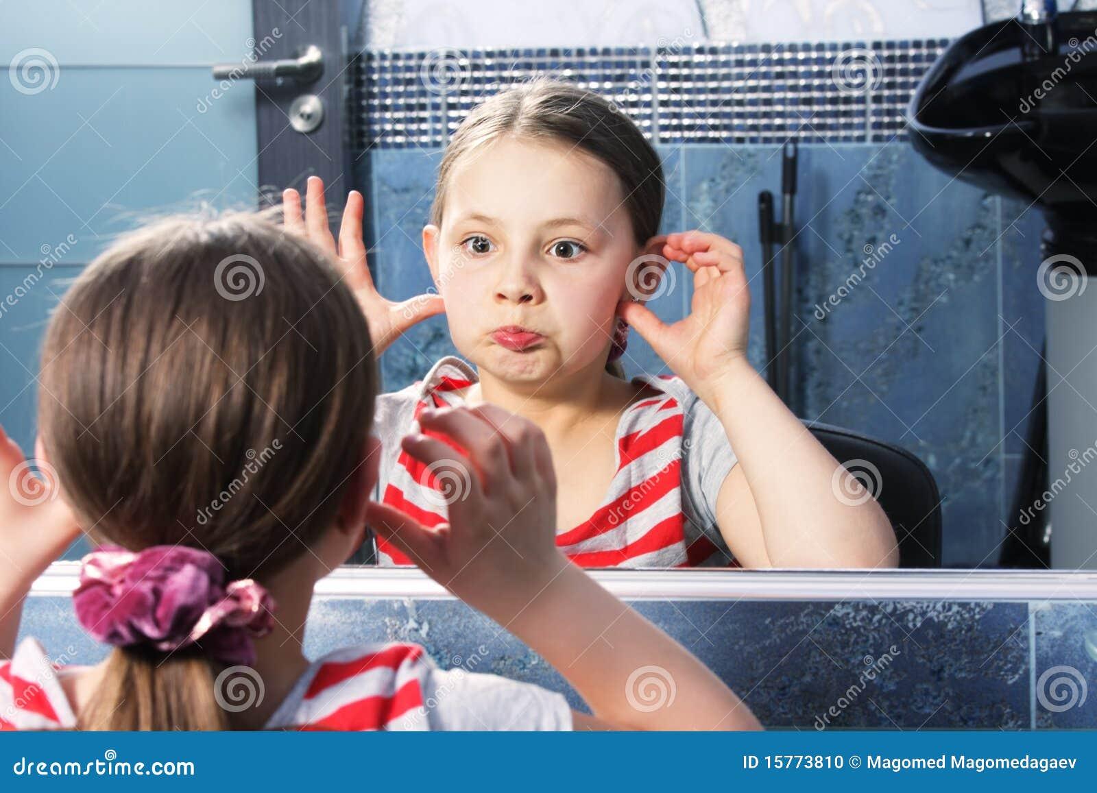 Ragazza che fa smorfie allo specchio fotografia stock - Ragazza davanti allo specchio ...