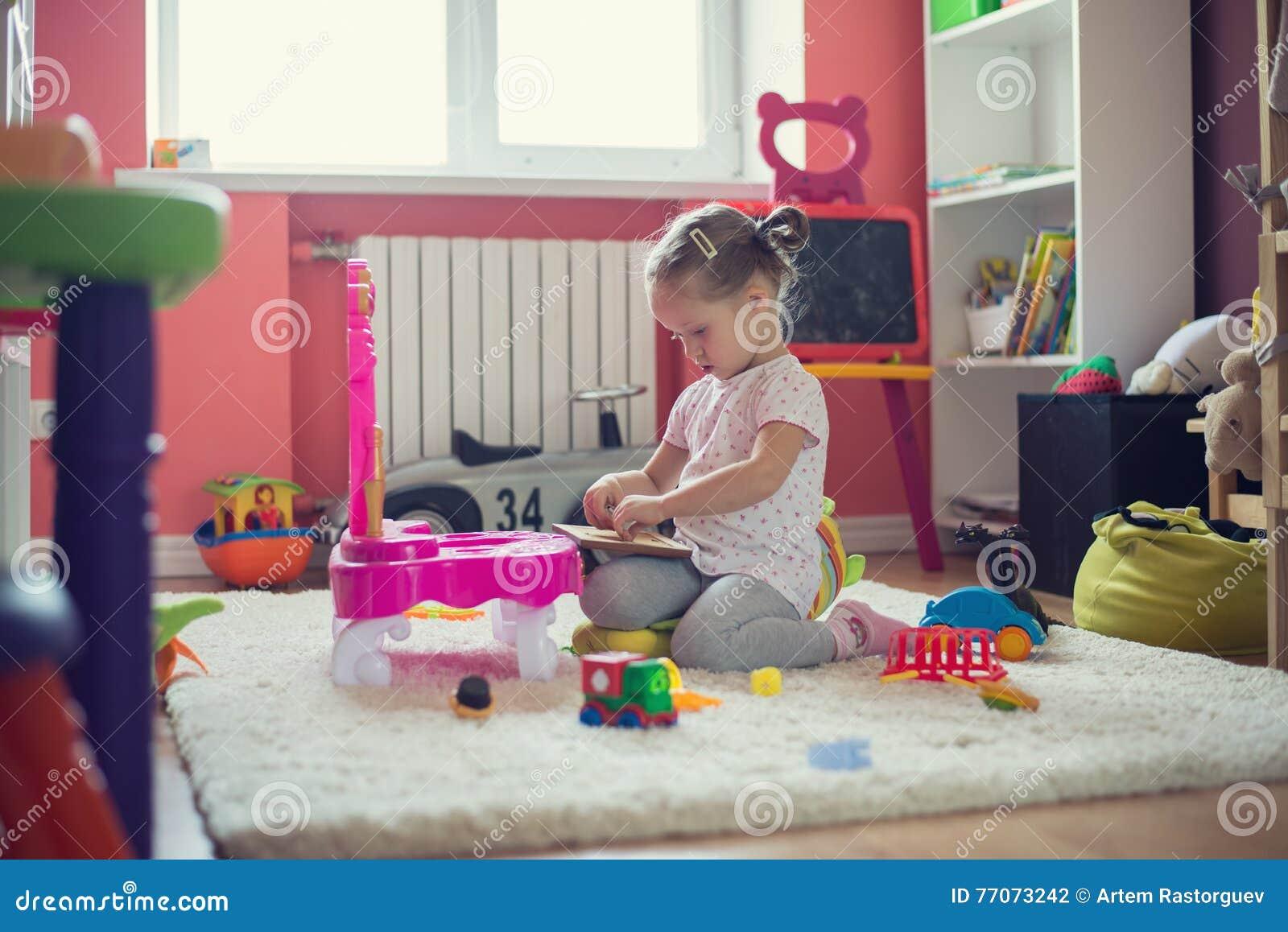 Ragazza che gioca con i giocattoli nella stanza di bambini