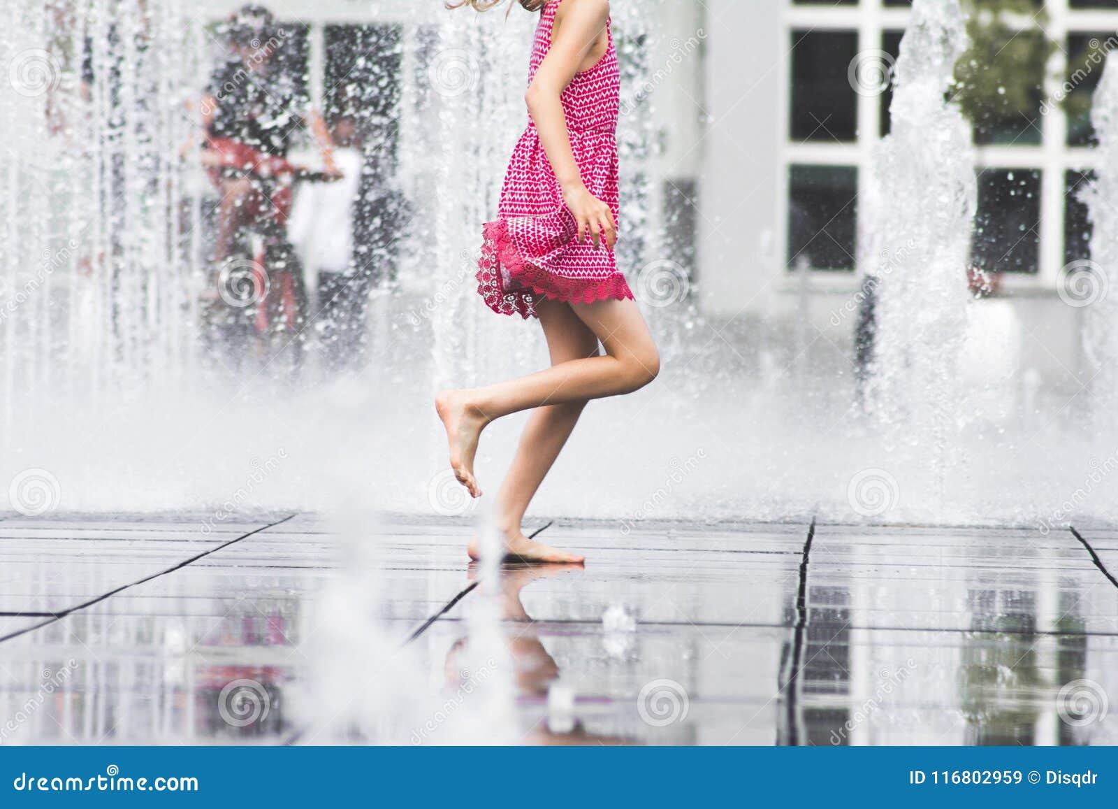 Ragazza che gode dell estate che corre liberamente attraverso l acqua della fontana