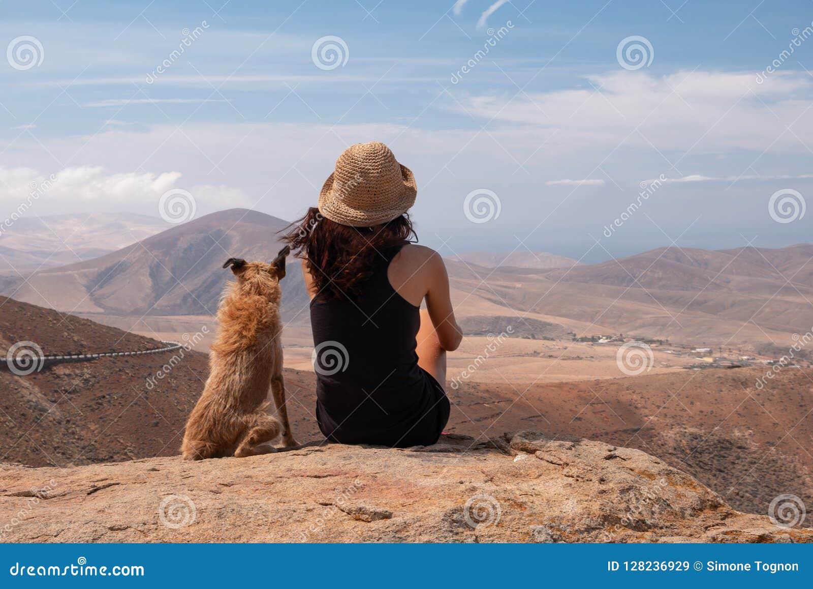 Ragazza che guarda il panorama con il suo cucciolo di cane