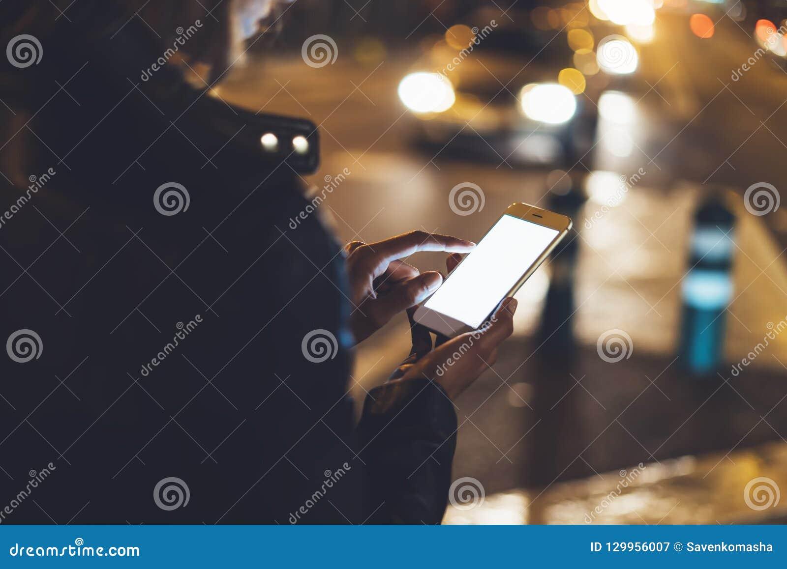 Ragazza che indica dito sullo smartphone dello schermo sulla luce in via atmosferica della città di notte, usando del bokeh del f