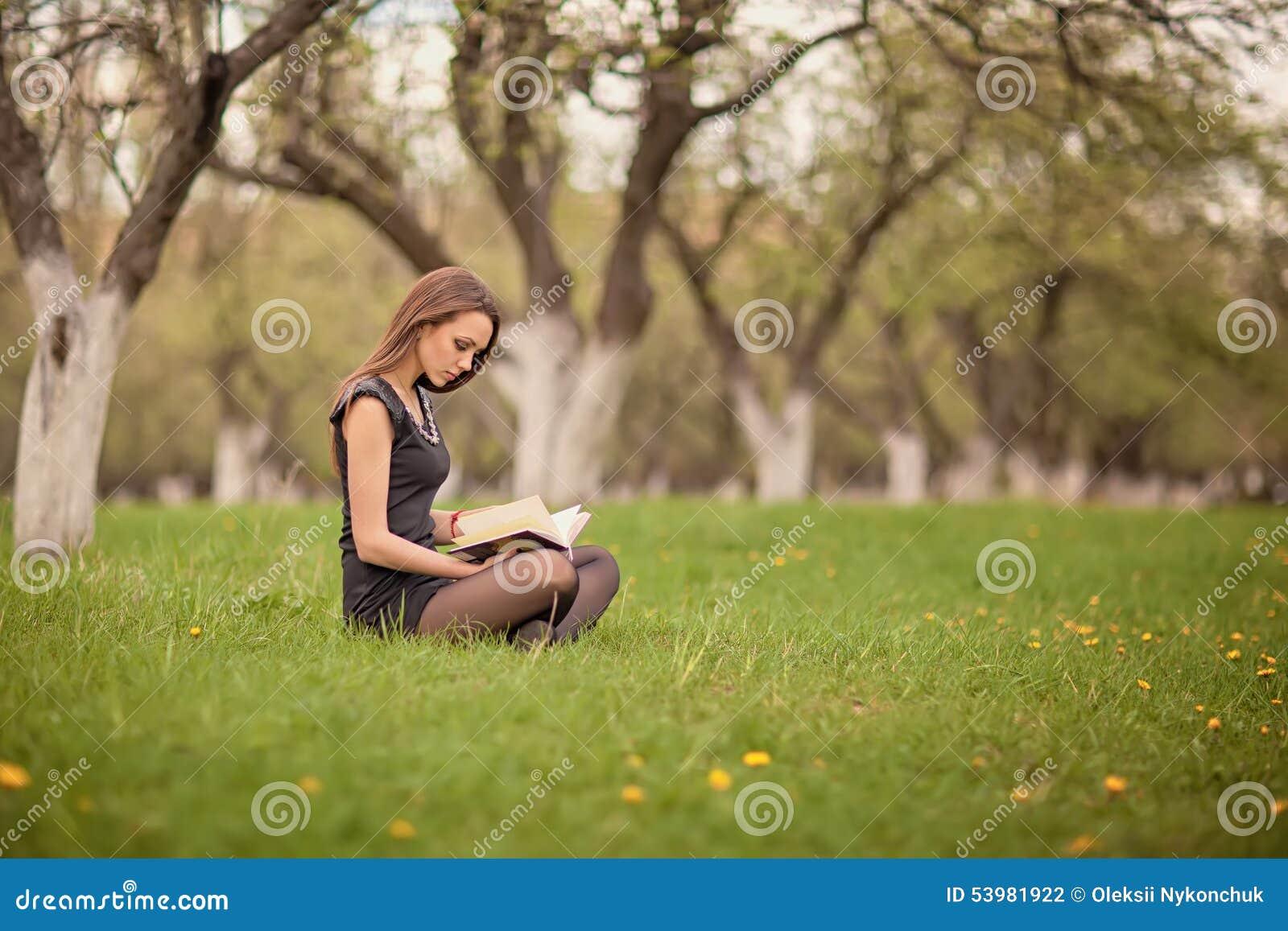 Ragazza che legge un libro sul prato inglese verde