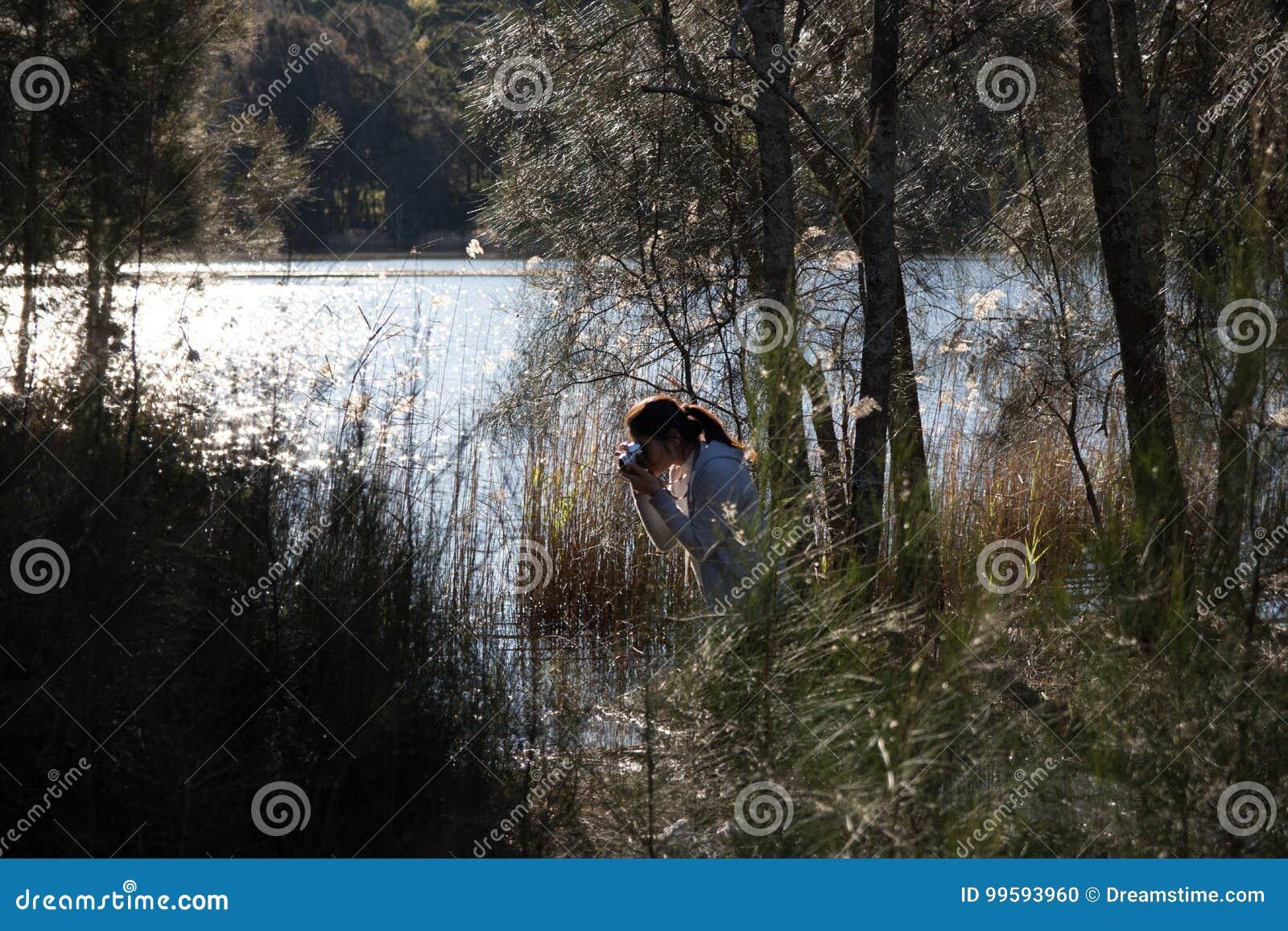 Ragazza che prende le foto della natura alla riva