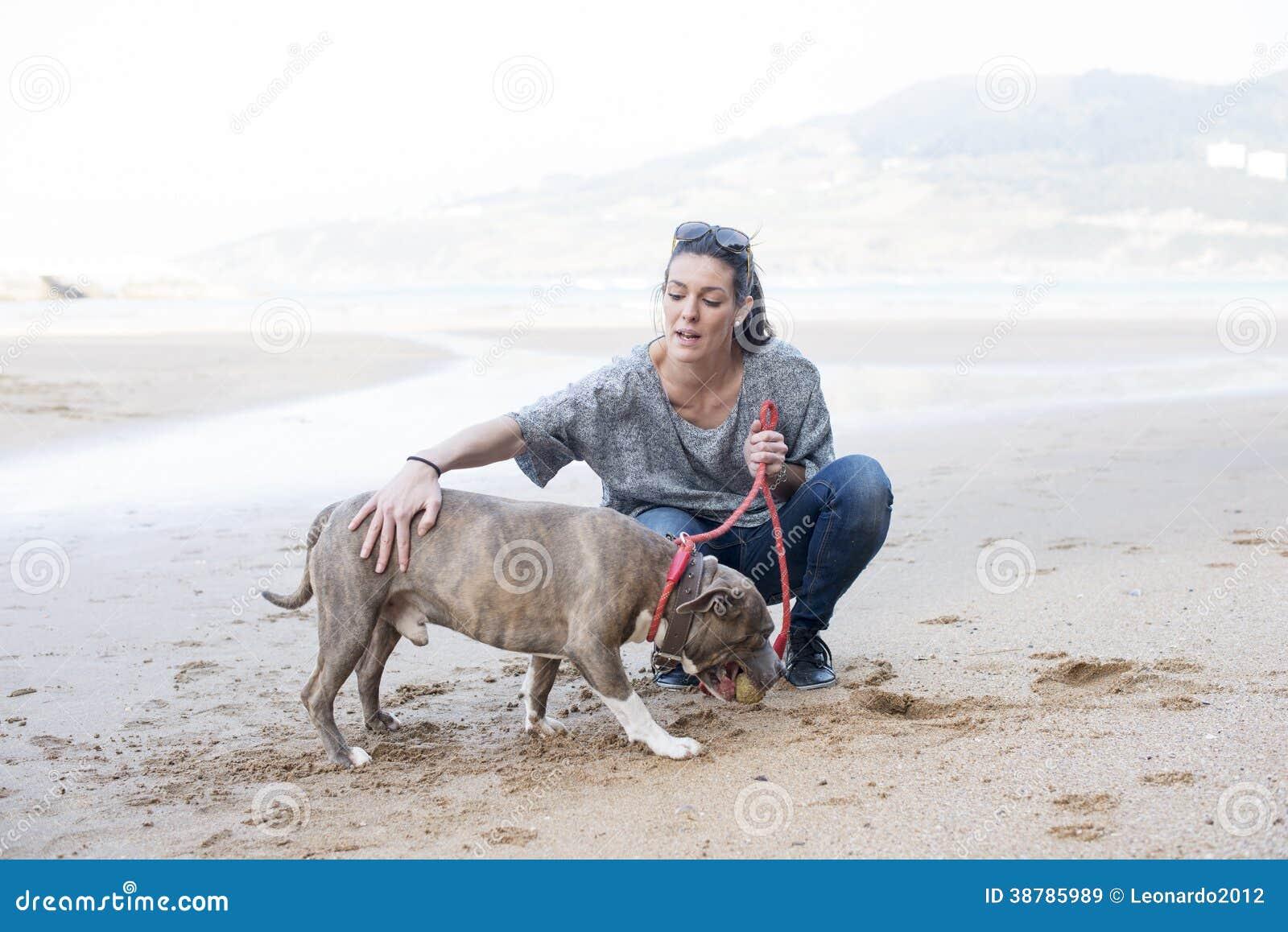 Ragazza che prepara il cane nella spiaggia.