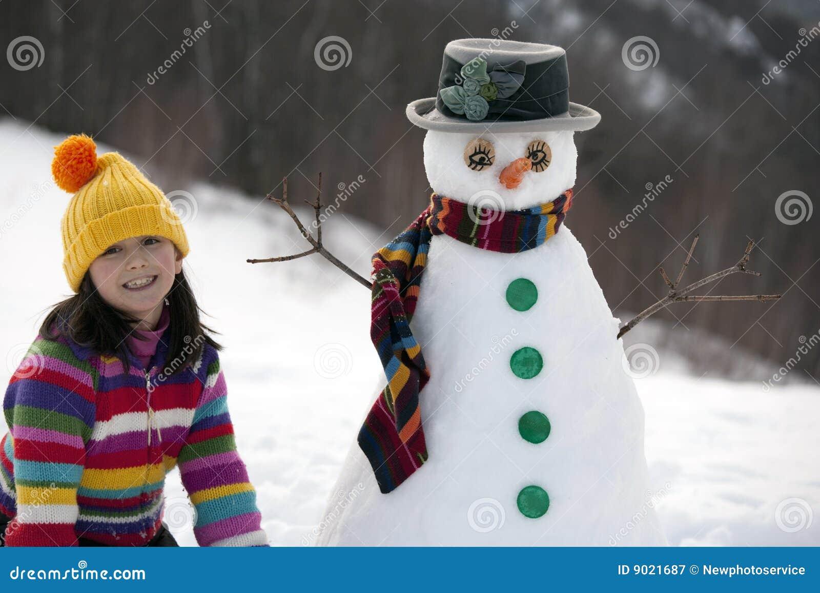 Ragazza che propone con il suo pupazzo di neve