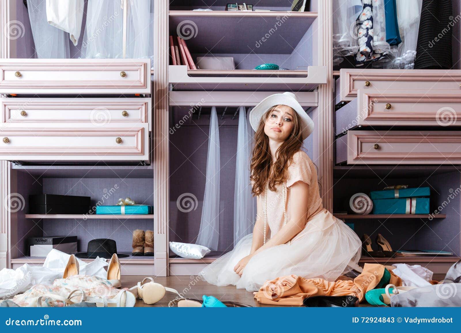 0a035c6820d1 Giovane bella ragazza pensierosa che sceglie i vestiti nel suo guardaroba
