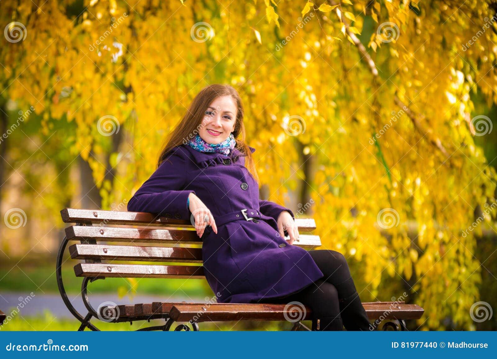 Ragazza che si siede il giorno caldo di autunno del banco