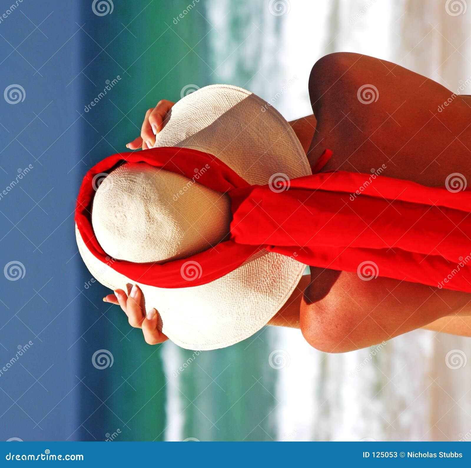 Ragazza che si siede sulla spiaggia sabbiosa al sole che registra cappello. Cielo blu, sciarpa blu di colore rosso del mare. La Sp