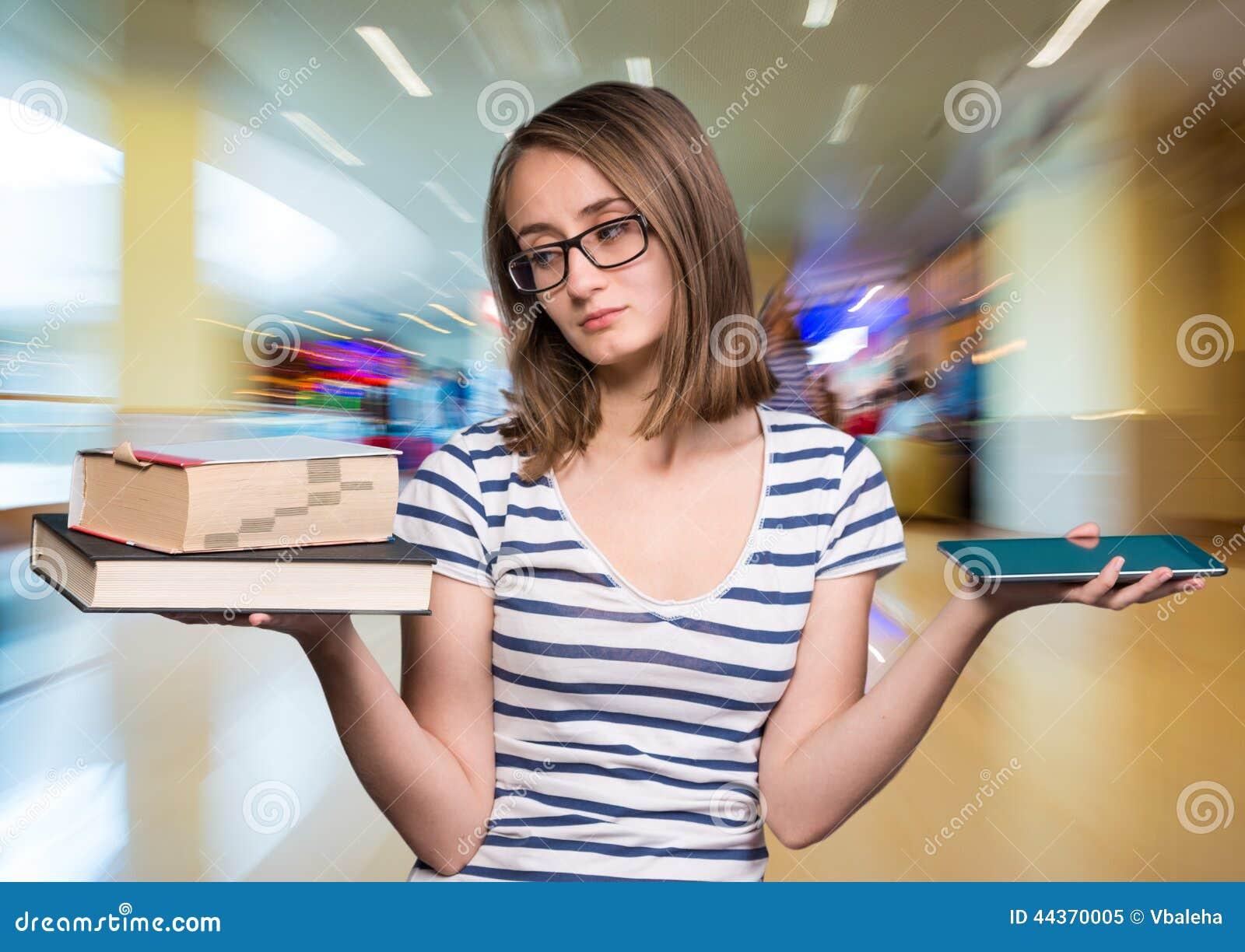 Ragazza che tiene un libro in una mano ed in un compressa-pc nel oth