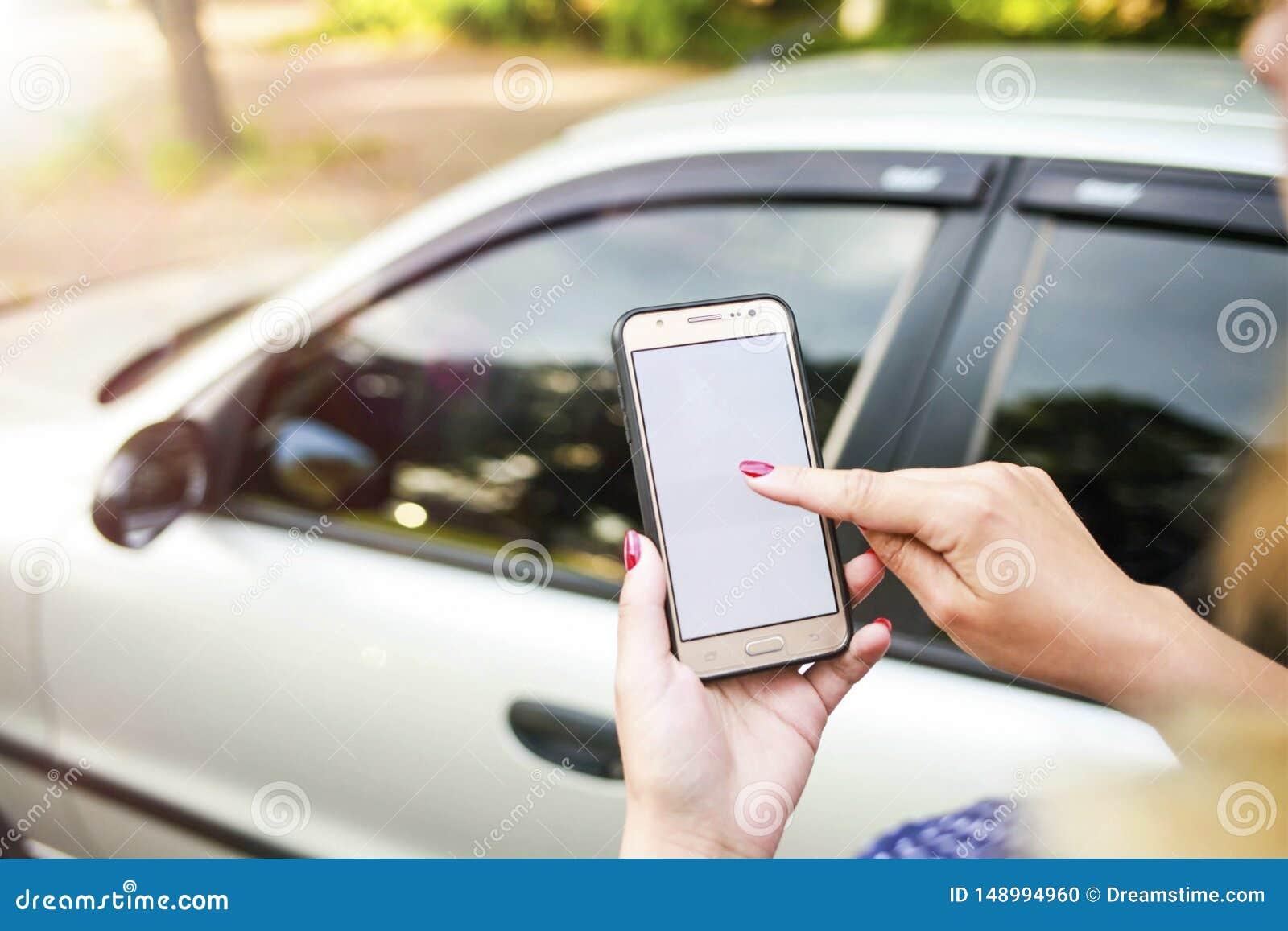 Ragazza che tiene un telefono nei precedenti dell automobile Autonoleggio di tema facendo uso del car sharing del telefono