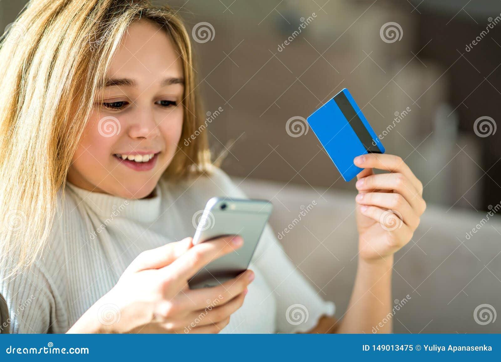 Ragazza che tiene una carta di credito e che per mezzo del telefono cellulare