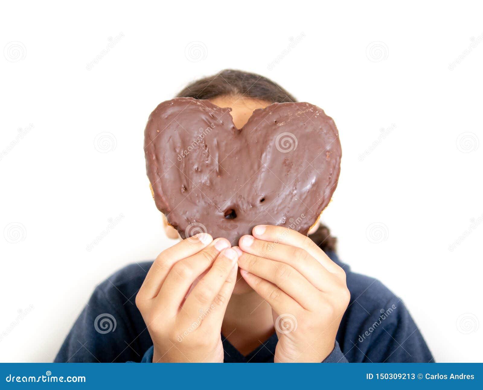 Ragazza che tiene una pasta sfoglia in forma di cuore