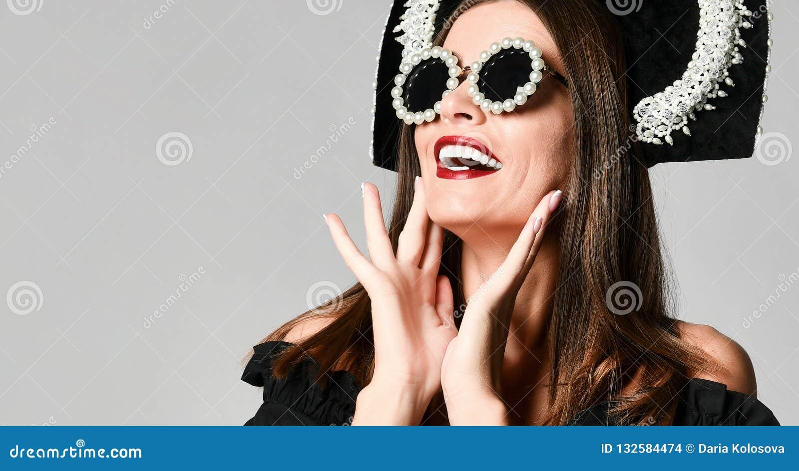 Ragazza colpita elegante, in vestito nero con gli occhiali da sole