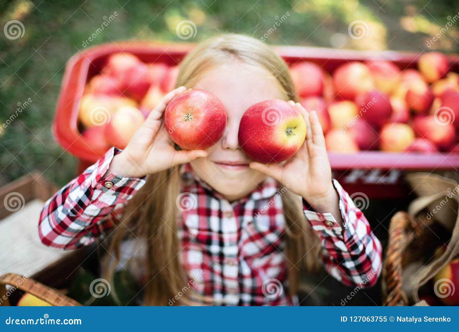 Ragazza con Apple nel meleto Bella ragazza che mangia Apple organico nel frutteto Concetto della raccolta Giardino, cibo del bamb