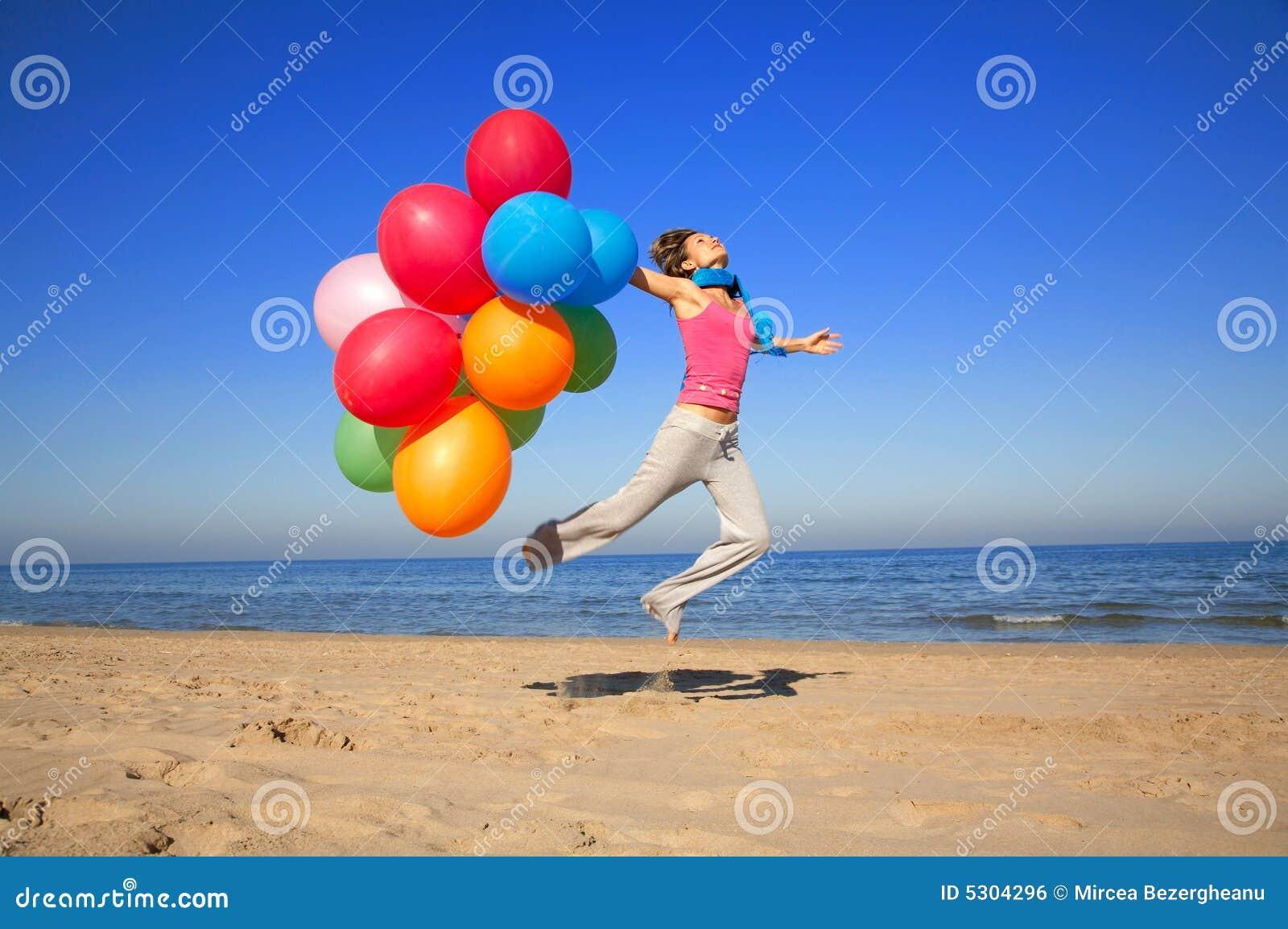 Download Ragazza Con Gli Aerostati Variopinti Che Saltano Sulla Spiaggia Fotografia Stock - Immagine di flessibilità, aerostato: 5304296