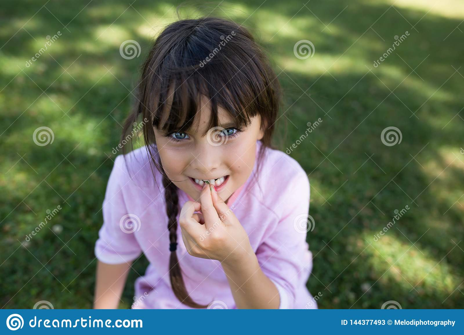 Ragazza con gli occhi azzurri che si siedono sull erba