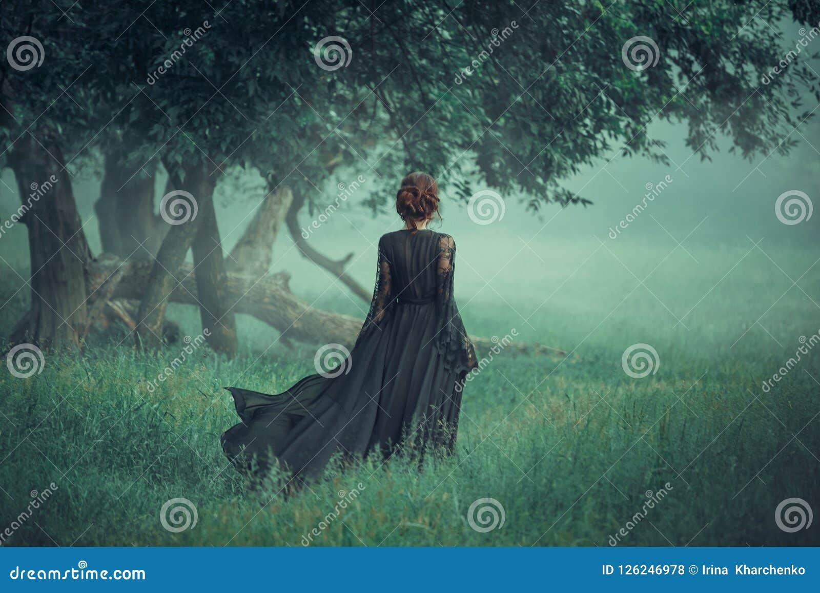 Ragazza con i capelli rossi che cammina avanti dalla foresta scura, vestito nero lungo d uso con il rimorchio che sta ondeggiando
