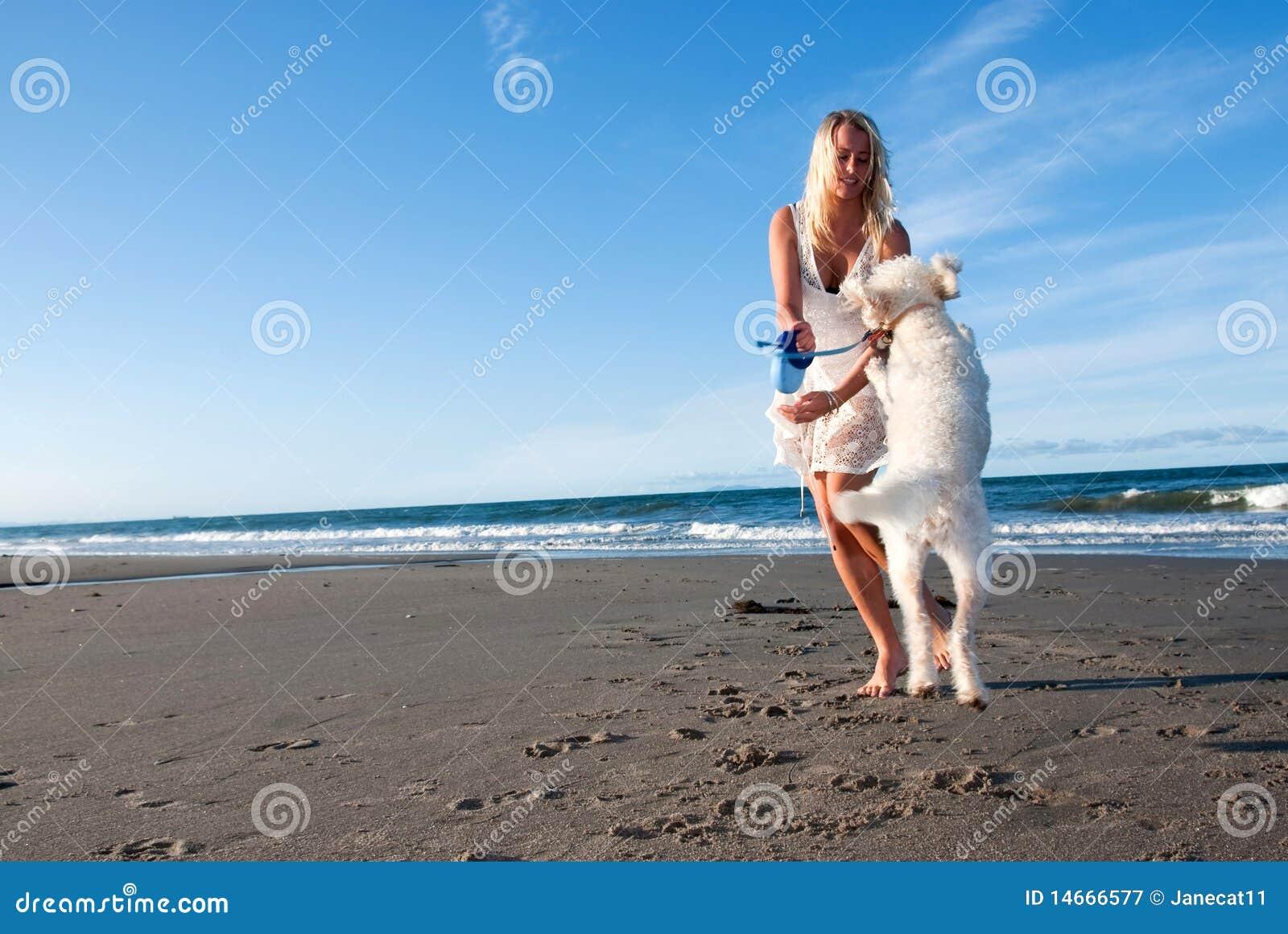 Ragazza con il cane alla spiaggia