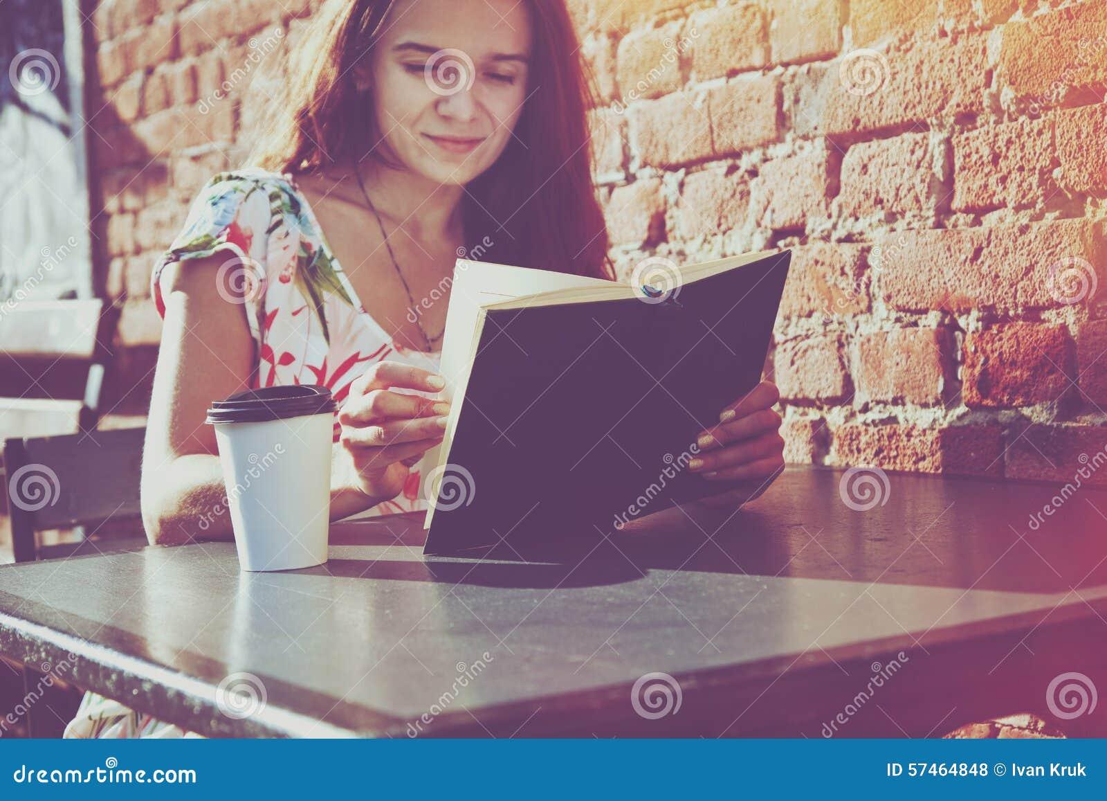 Ragazza con il libro di lettura del caffè