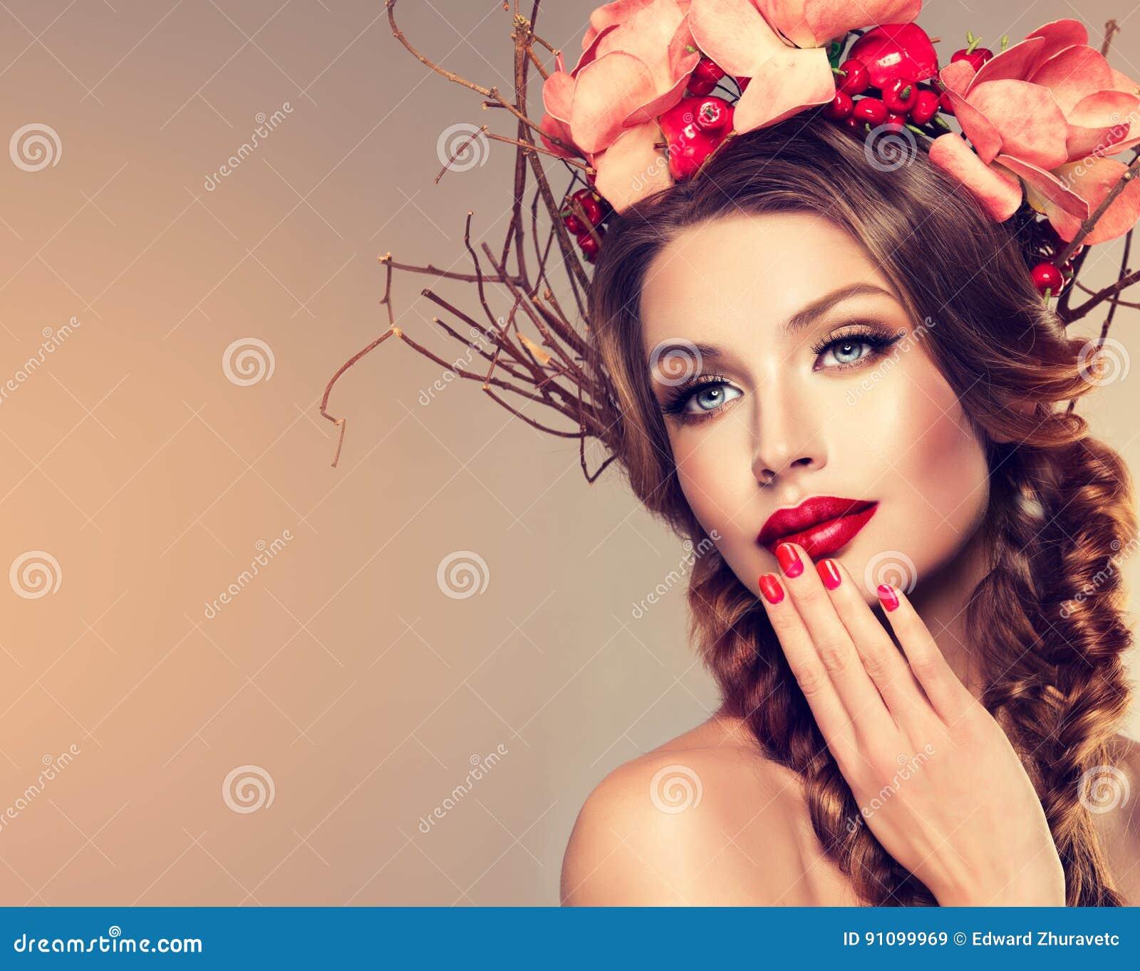 Ragazza con la corona delicata dai fiori, dai frutti e dai ramoscelli su lei capa