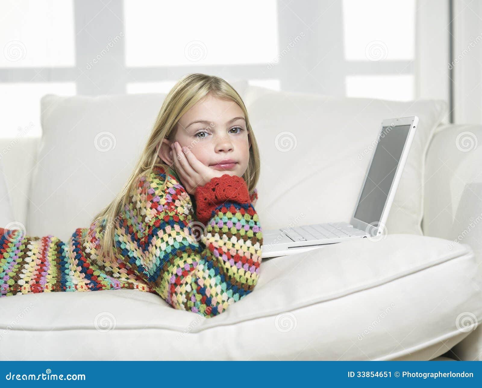 Ragazza con la mano su Chin Using Laptop On Sofa