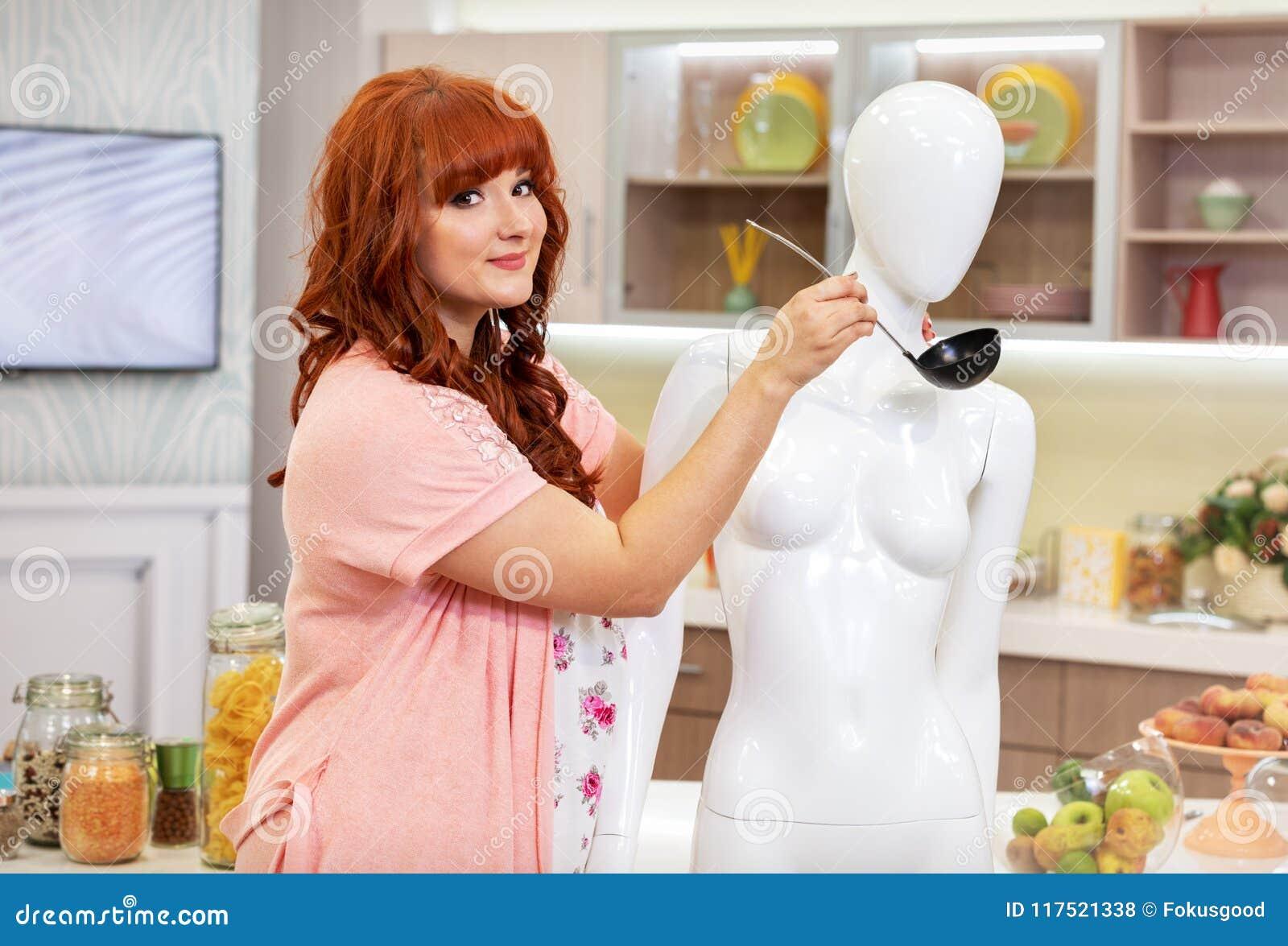 Ragazza con la siviera vicino al manichino in cucina