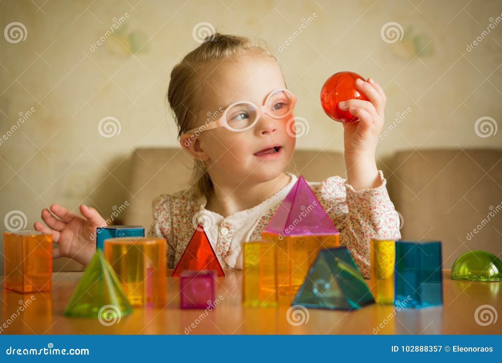Ragazza con sindrome di Down che gioca con le forme geometriche