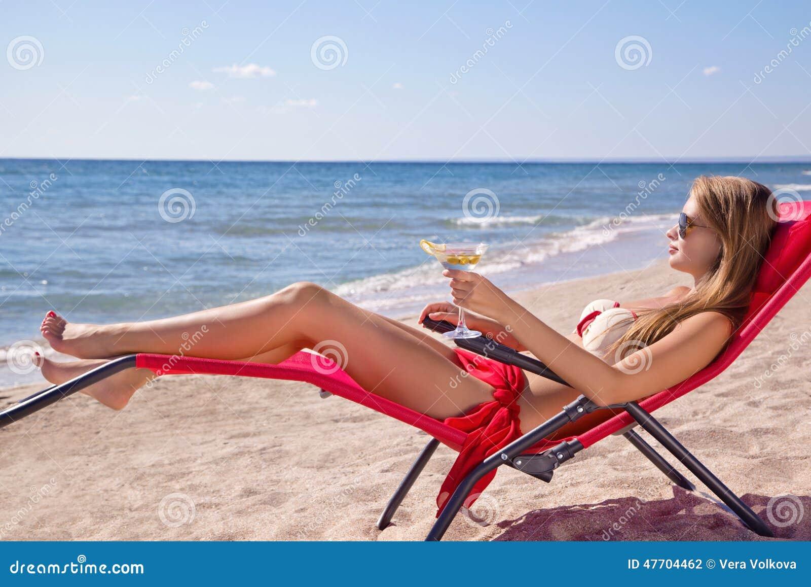 Ragazza con un cocktail martini sulla spiaggia