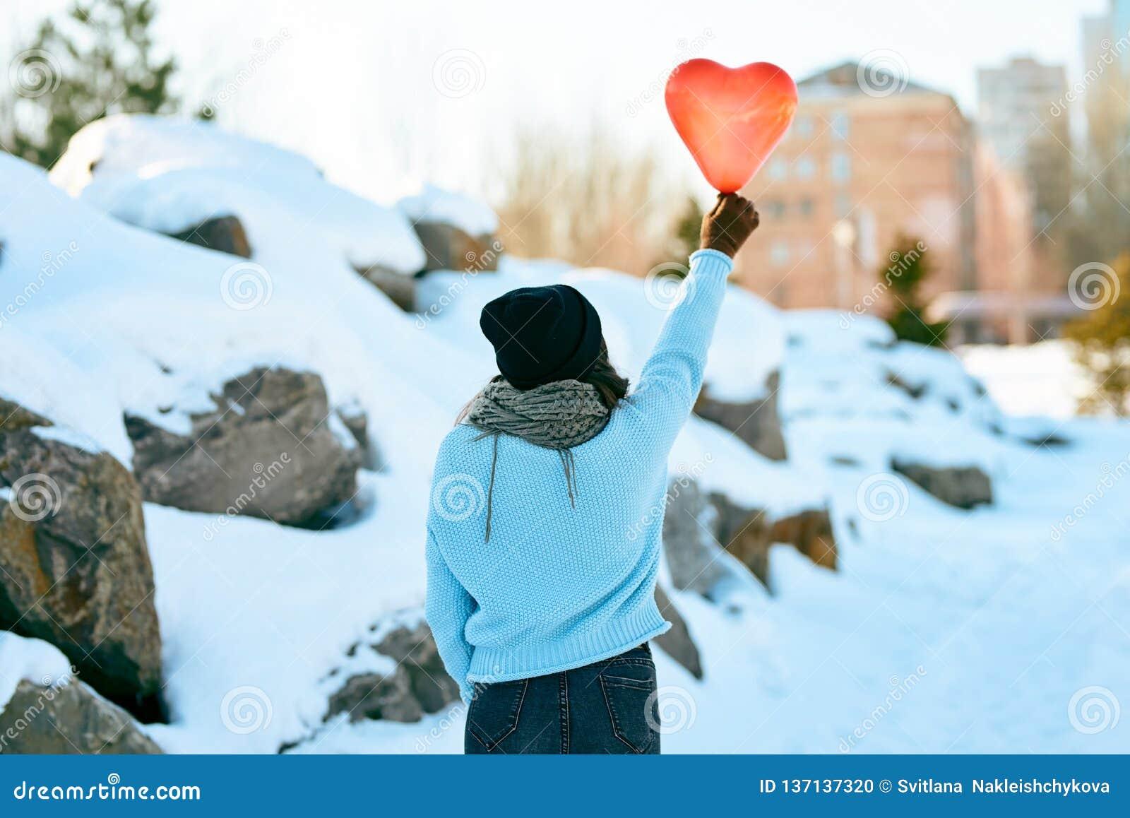 Ragazza con un pallone sotto forma di un cuore in mani Giorno del `s del biglietto di S