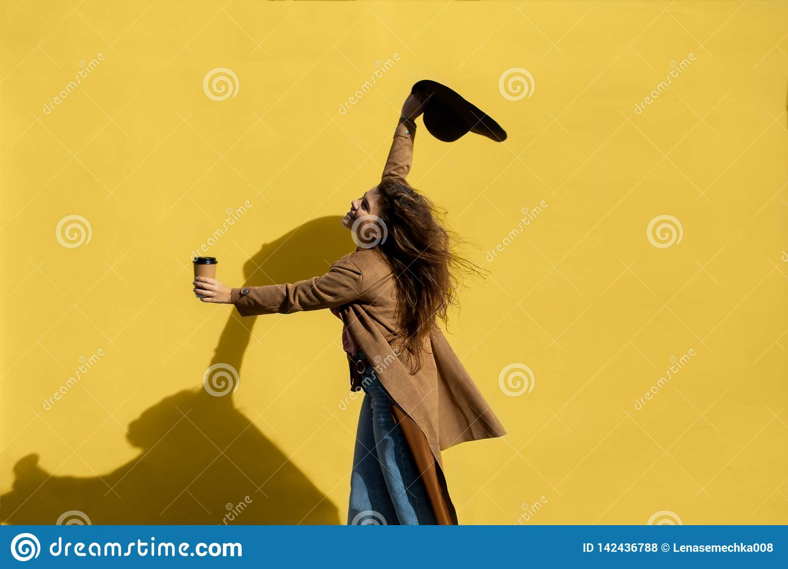 Ragazza con una tazza di caffè un giorno soleggiato vicino alla parete gialla
