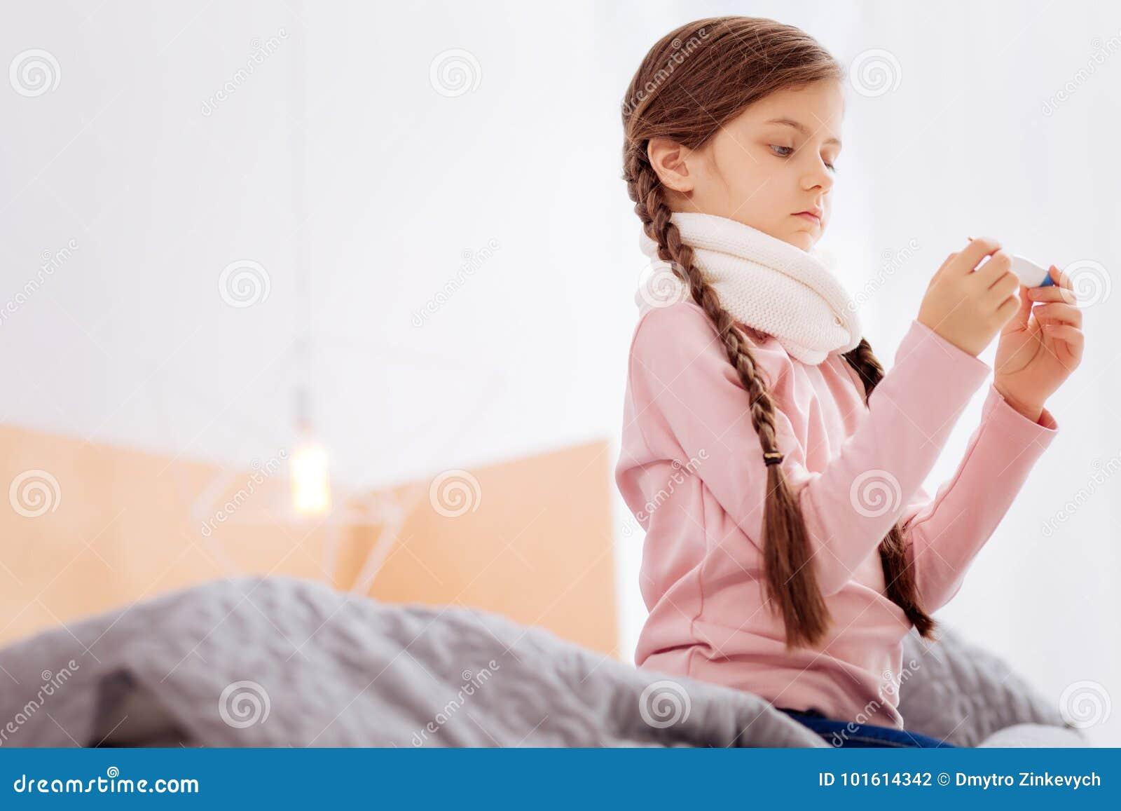 Ragazza curiosa che misura la temperatura mentre sedendosi sul letto