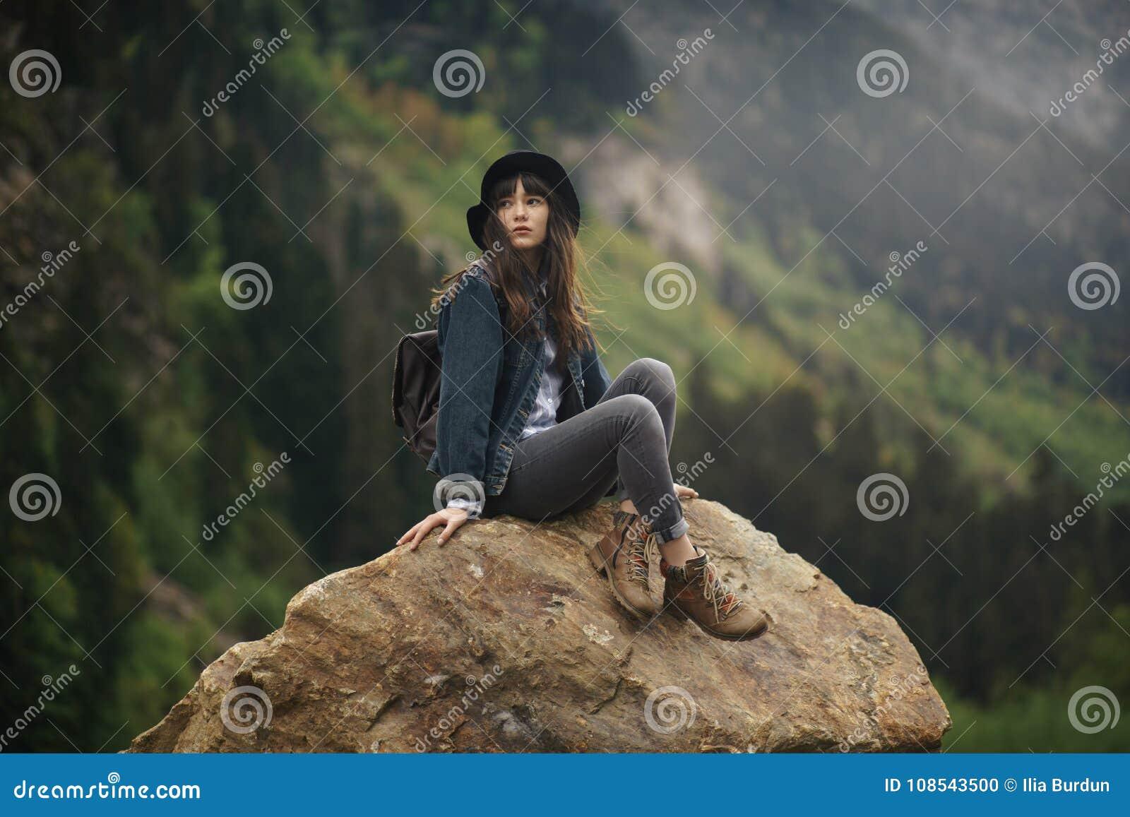 Ragazza dei pantaloni a vita bassa con lo zaino che gode del tramonto sulla montagna di punta Viaggiatore turistico sulla vista d