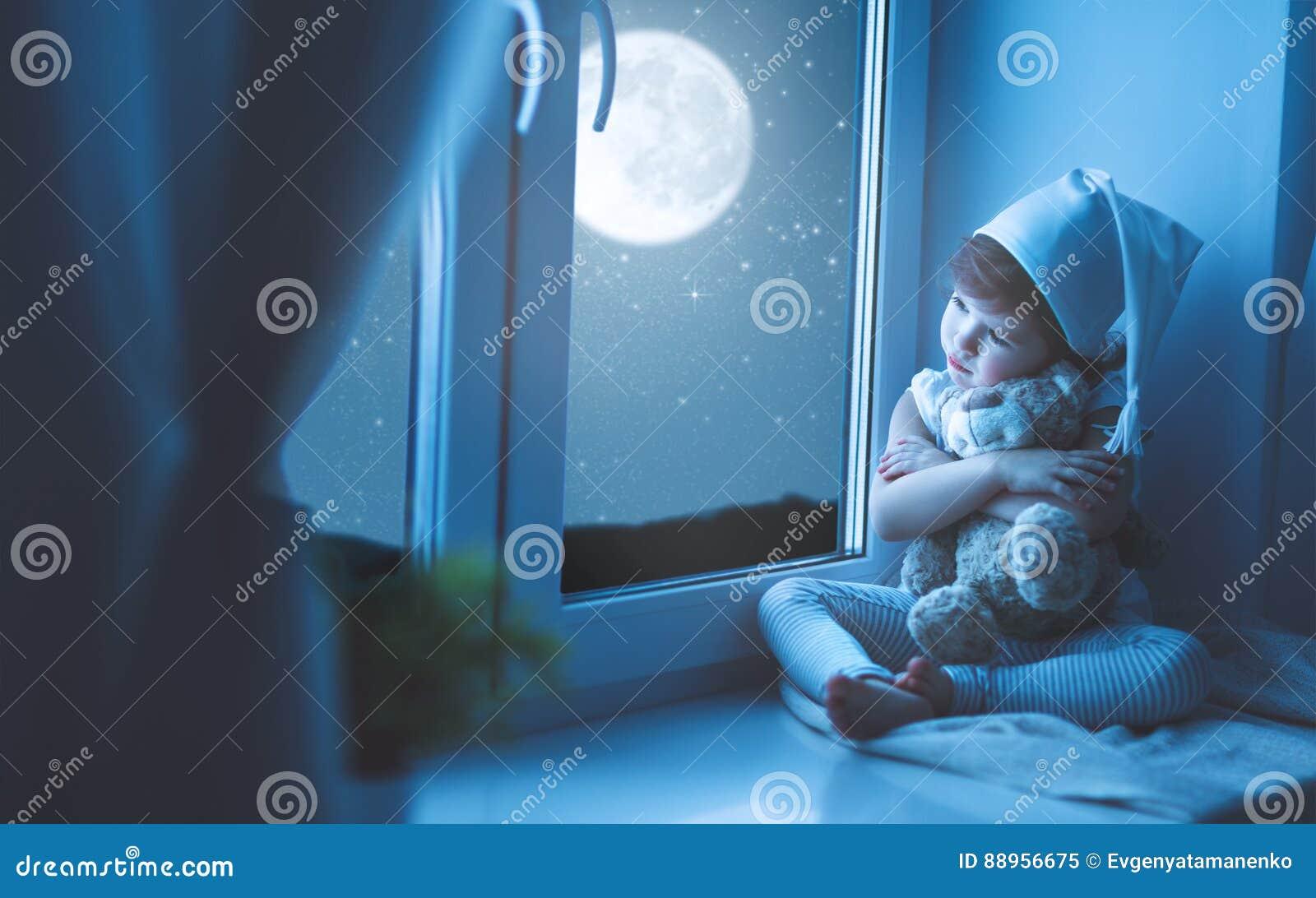 Ragazza del bambino alla finestra che sogna cielo stellato all ora di andare a letto