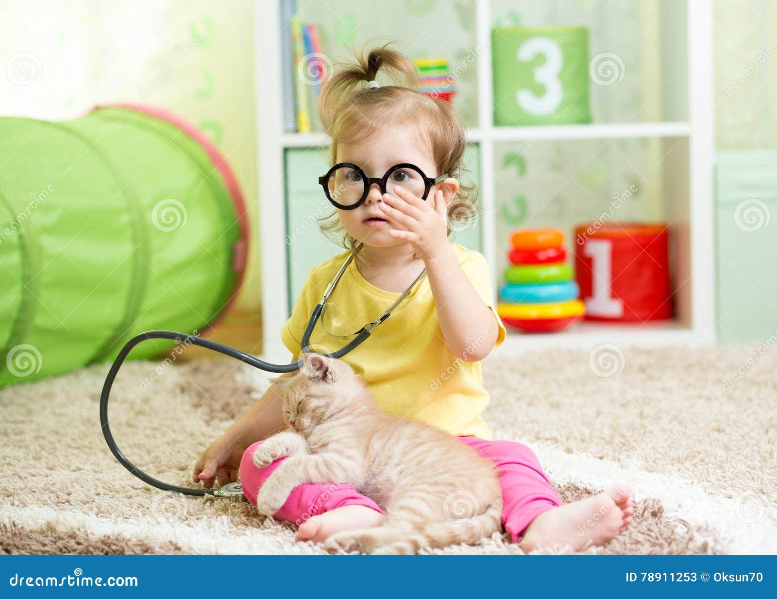 Ragazza del bambino che gioca al dottore With Cat In Nursery