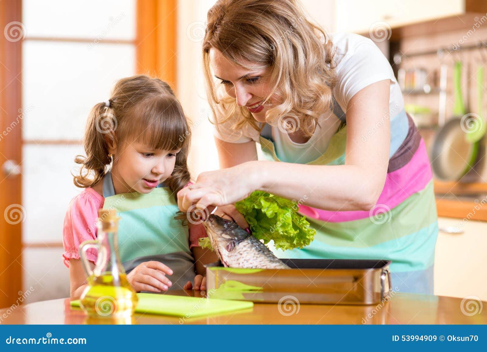 Ragazza del bambino con la mamma che cucina pesce nella for Konzentrationsschw che kind