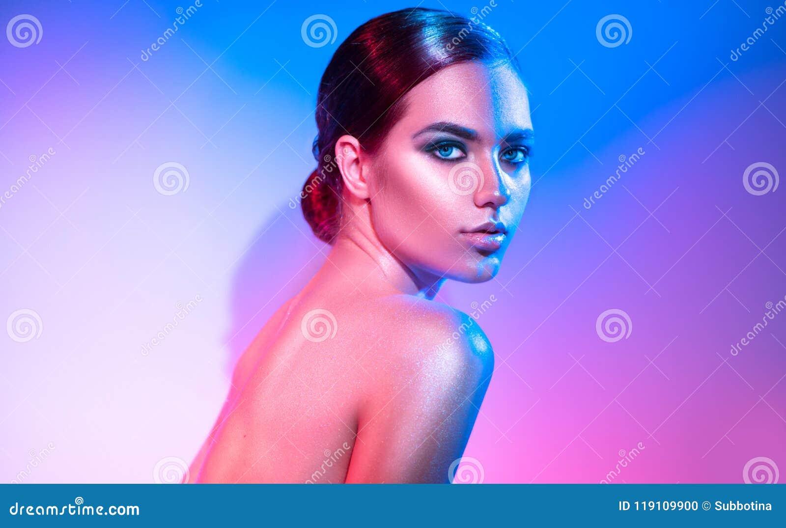 Ragazza del modello di alta moda nelle scintille luminose variopinte e nelle luci al neon che posano nello studio Ritratto di bel