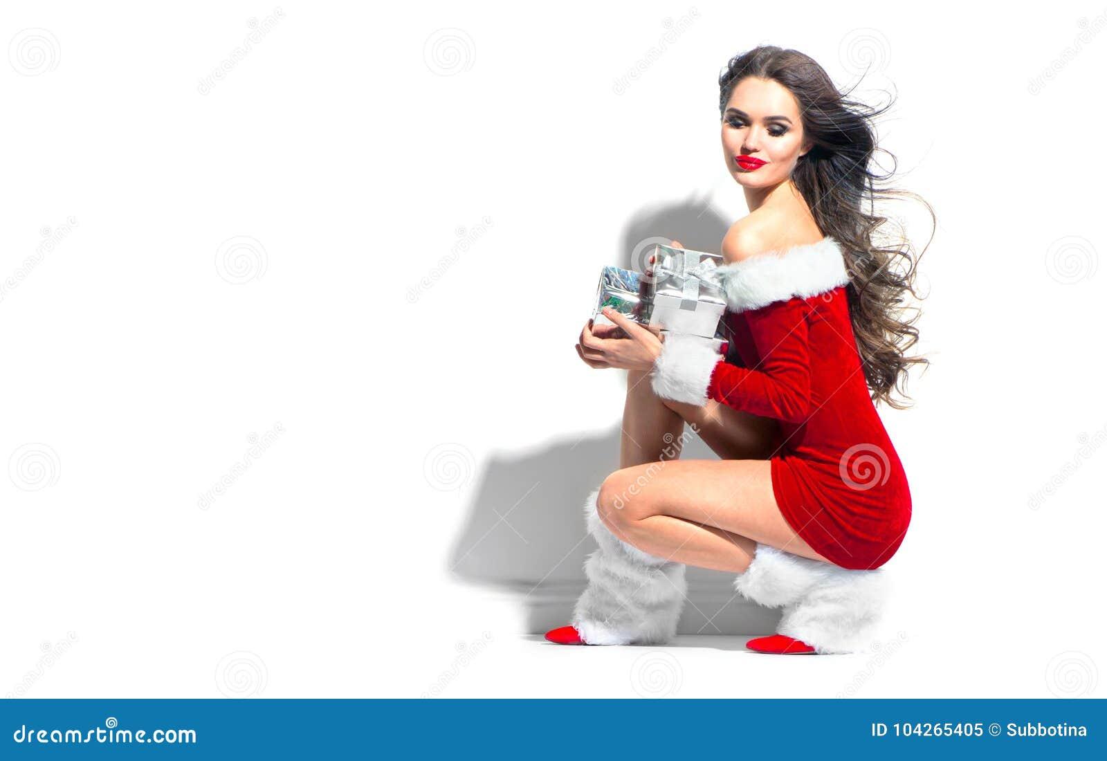 Ragazza del modello di bellezza di Natale che indossa i regali rossi della tenuta del vestito da Santa Giovane donna castana sexy