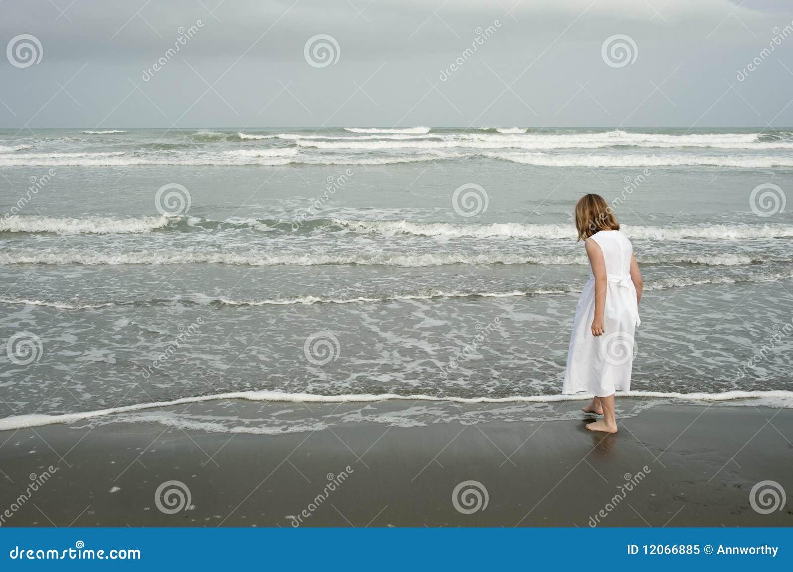 Ragazza del vestito dalla spiaggia piccolo che gioca bianco
