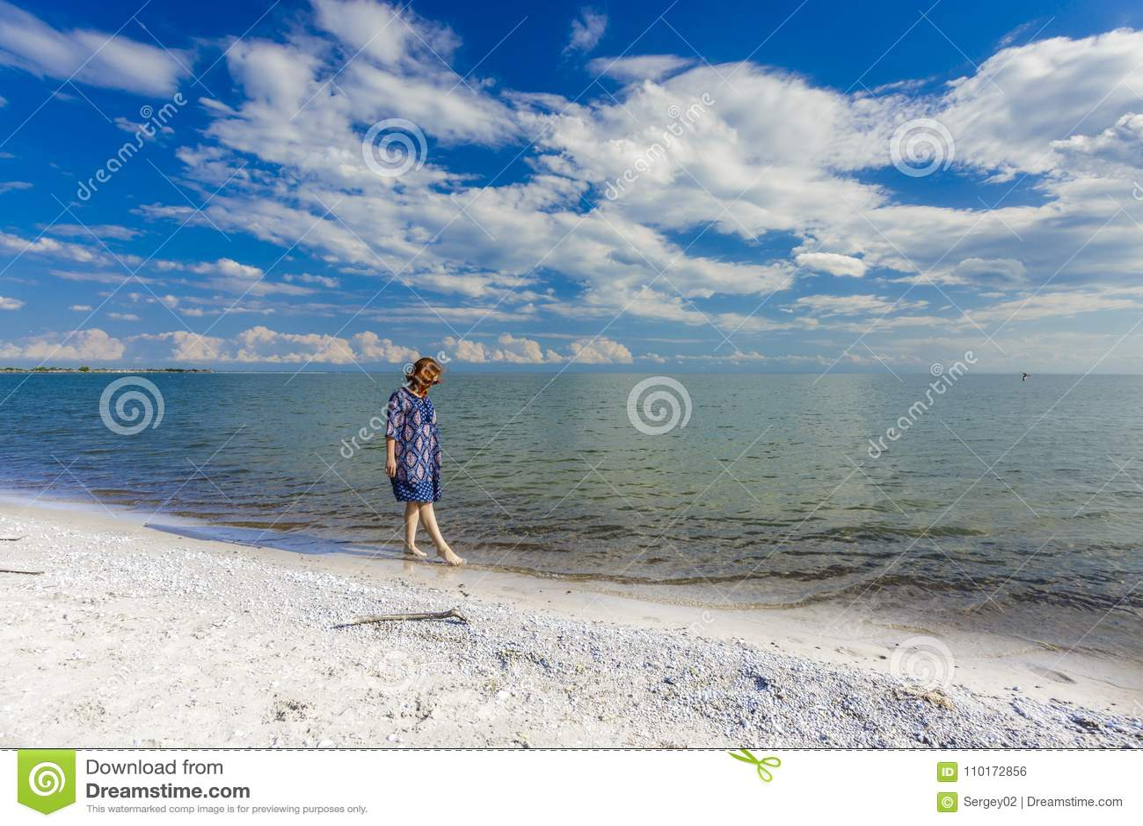 Ragazza dentro in vestito blu che cammina alla spiaggia del lago