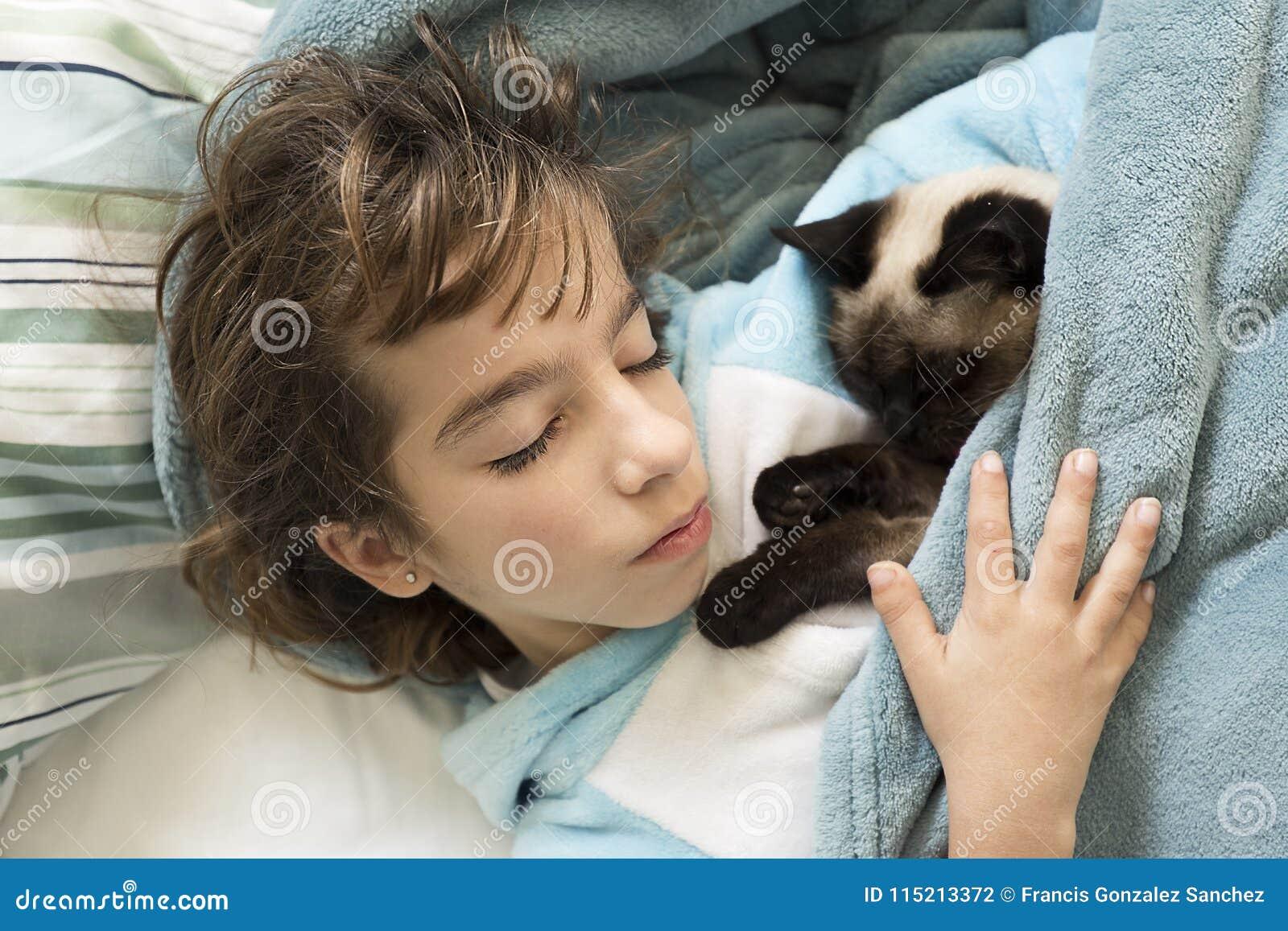 Ragazza di 10 anni che dorme a letto con il suo gatto sulla cima