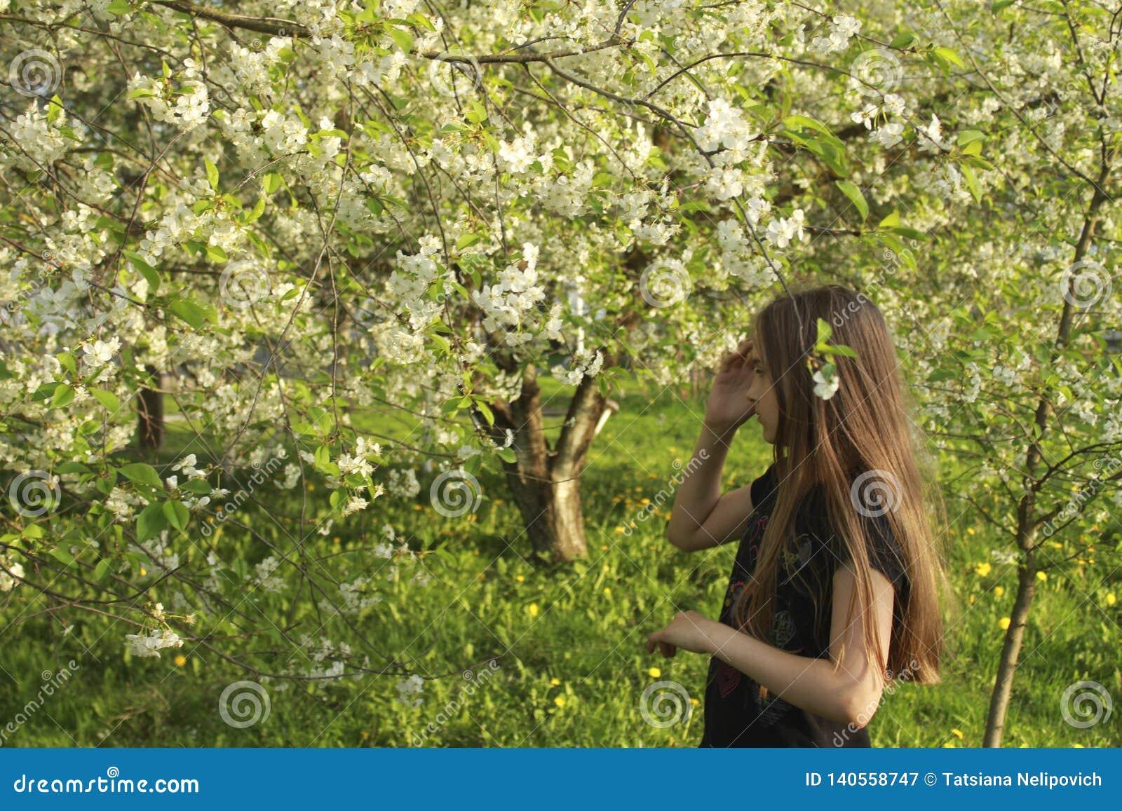 Ragazza di Beautifu nel giardino fiorito sbocciante della molla