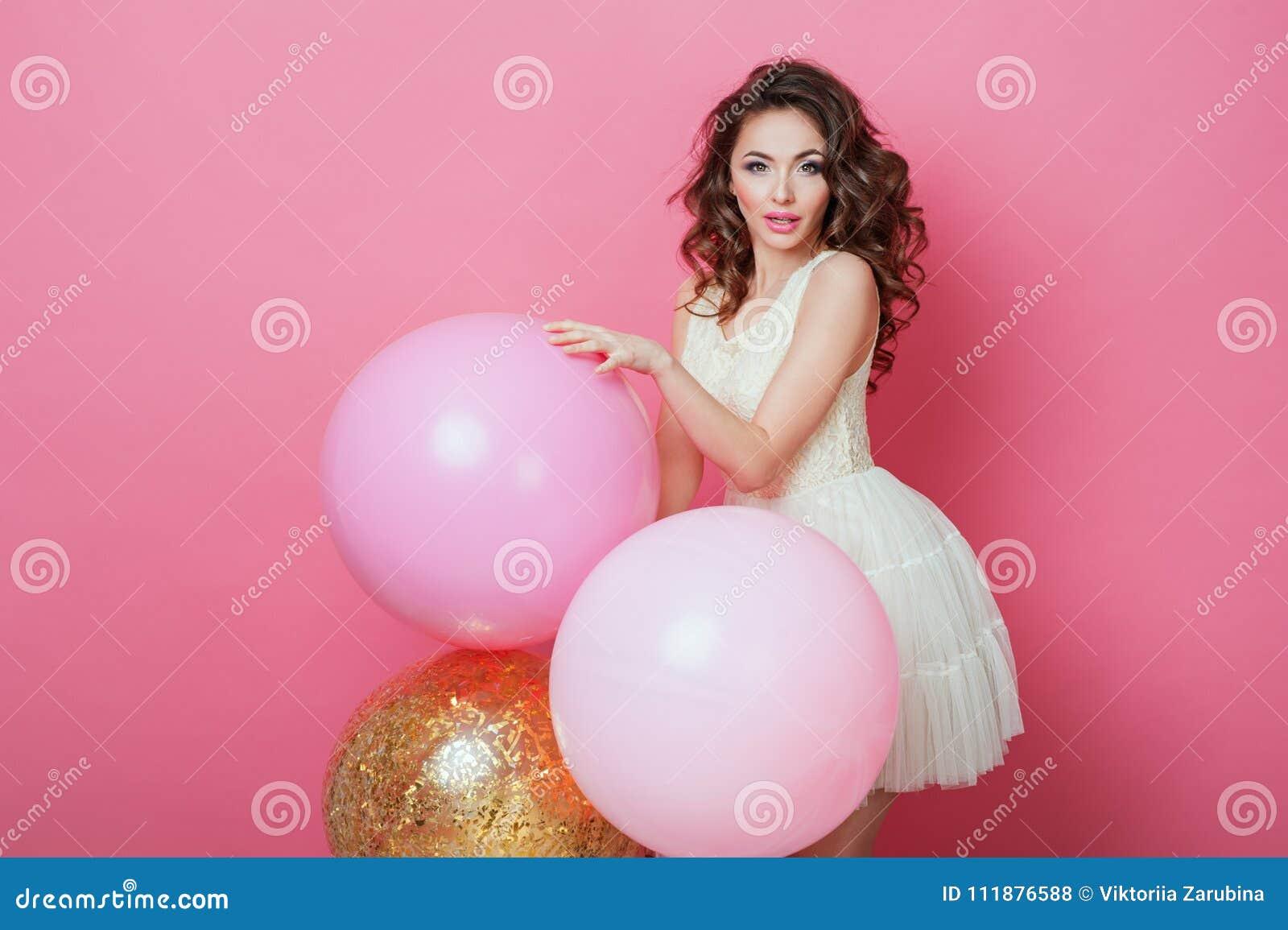 Ragazza di bellezza con gli aerostati variopinti che ride sopra il fondo rosa Bella giovane donna felice sul partito di festa di