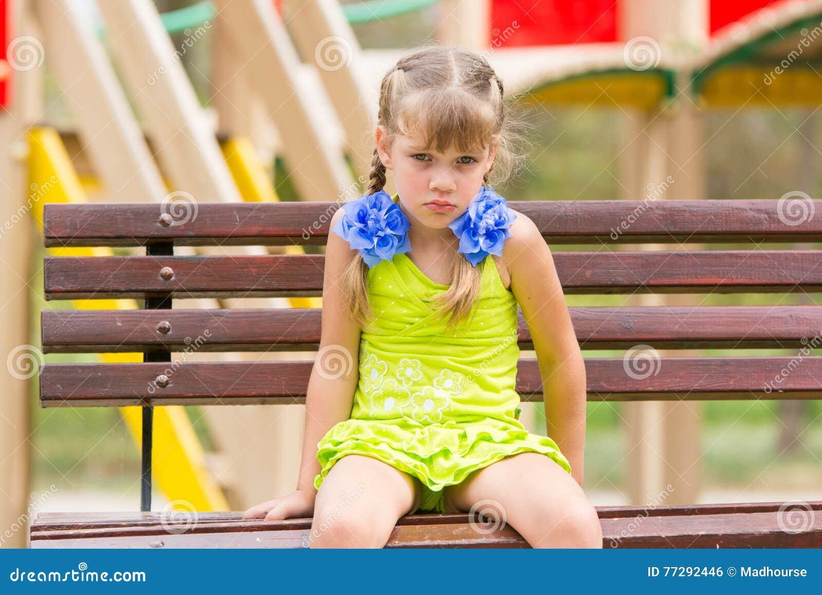Ragazza di cinque anni offensiva che si siede su un banco al campo da giuoco