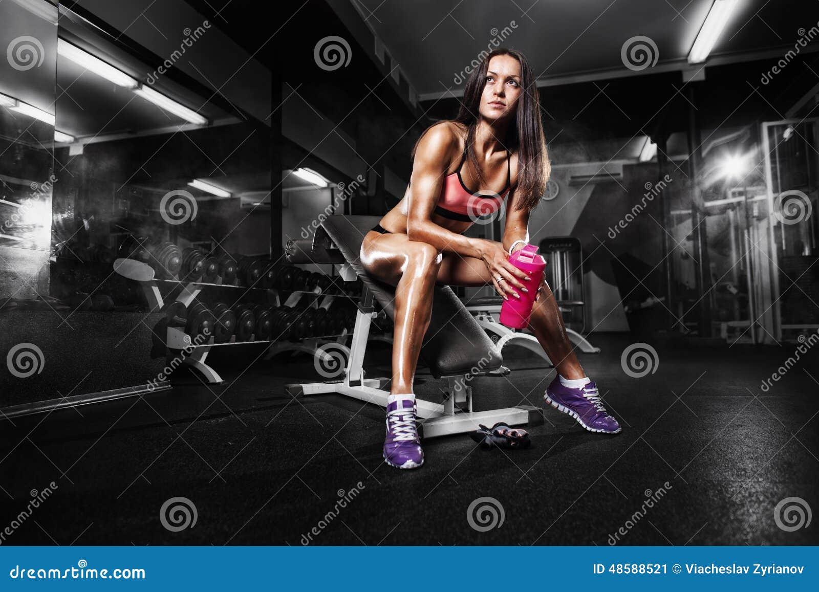 Ragazza di forma fisica con l agitatore che posa sul banco nella palestra